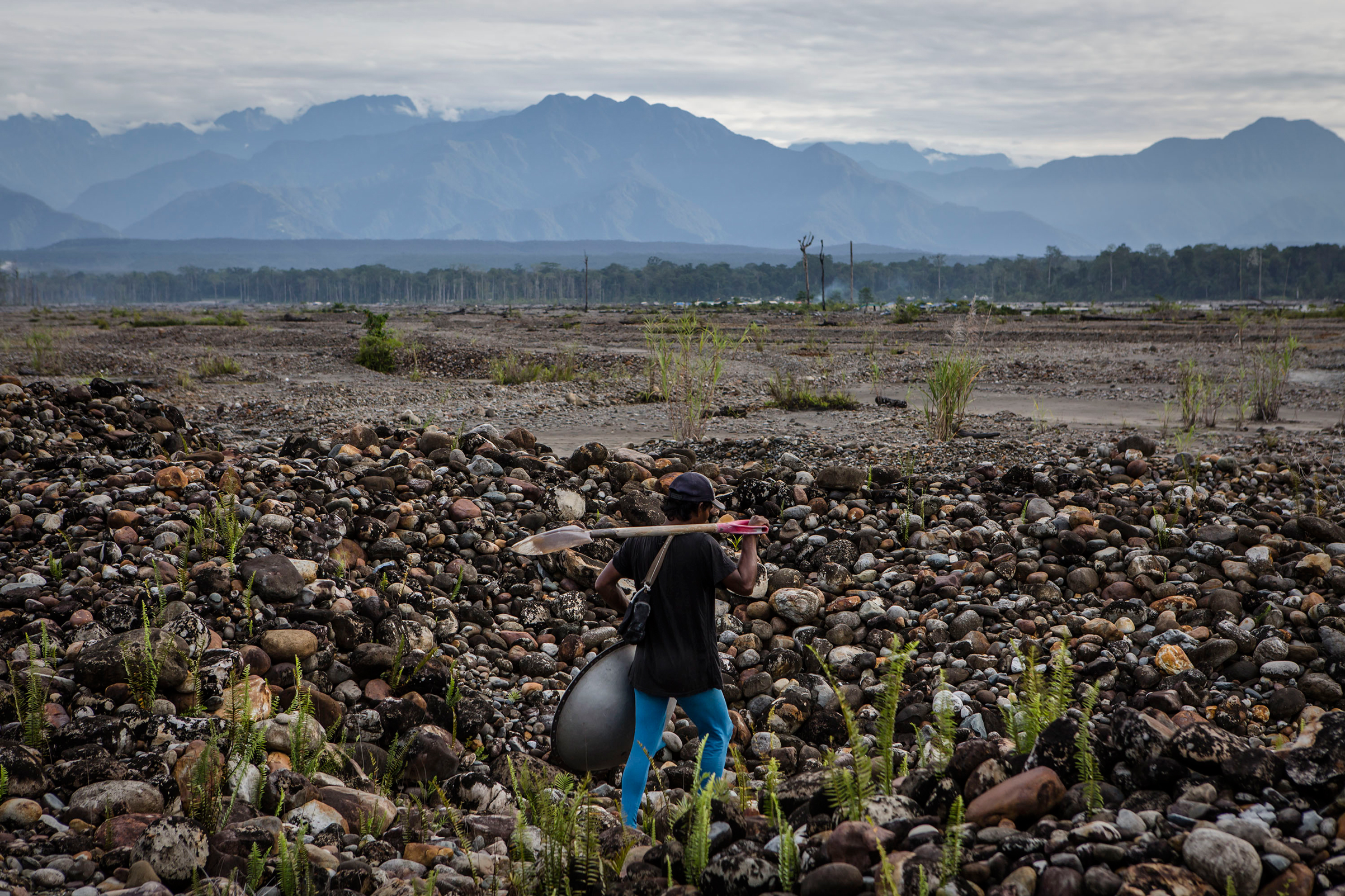 A illegal gold miner walks as they pan for gold along the Aikwa river are located within Freeport's official mining operations in Timika, Papua Province, Indonesia, on Feb. 4, 2017.