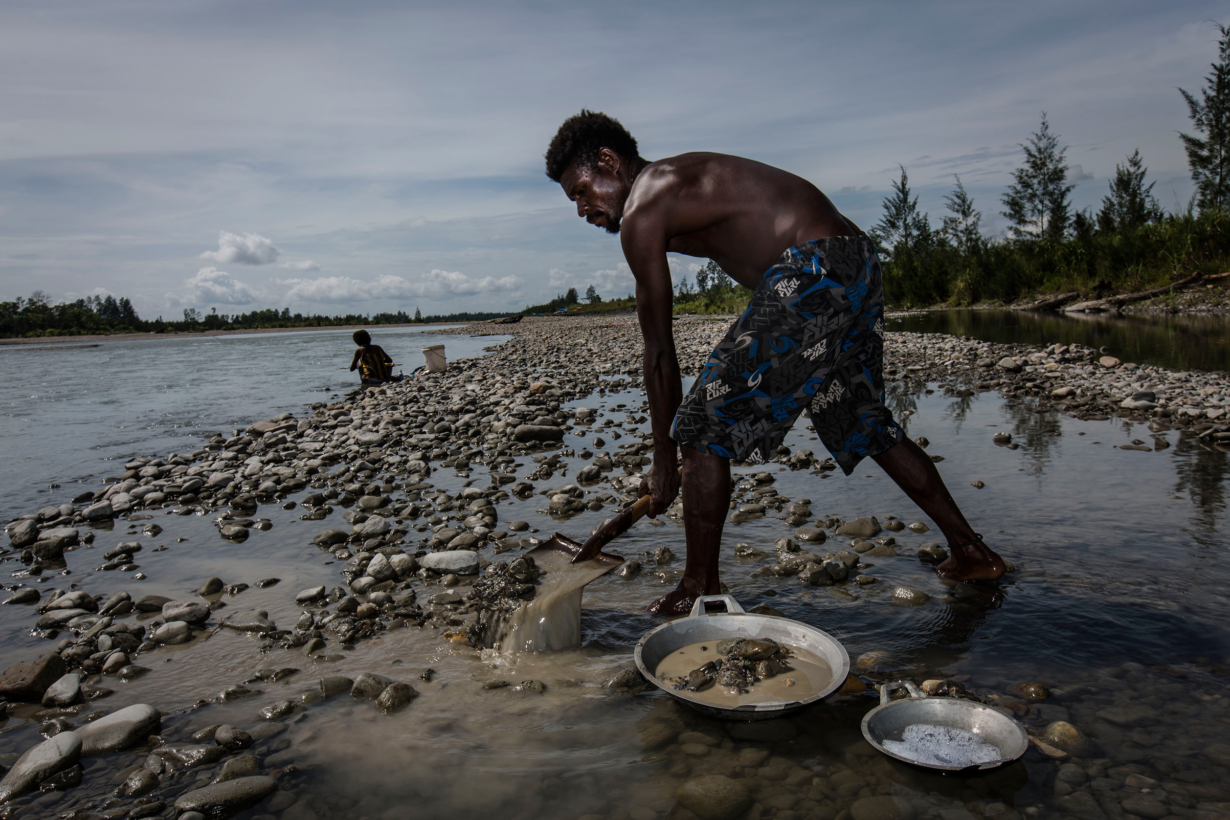 An illegal gold miner sifts through sand and rock as he pans for gold in Timika, Papua Province, Indonesia, on Feb. 4, 2017.