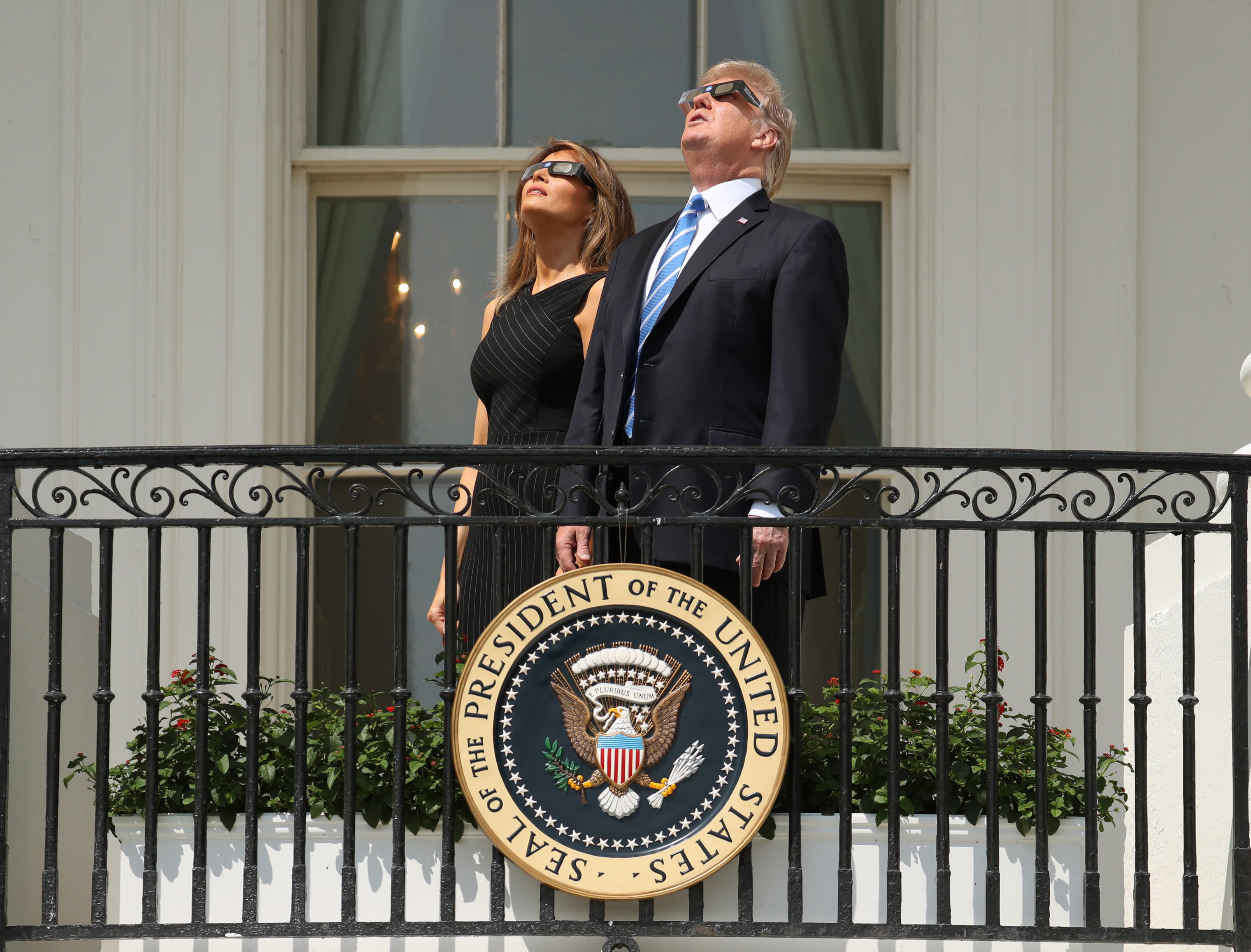 President Trump and First Lady Melania Trump wear protective glasses as they view the solar eclipse at the White House in Washington on Aug. 21, 2017.