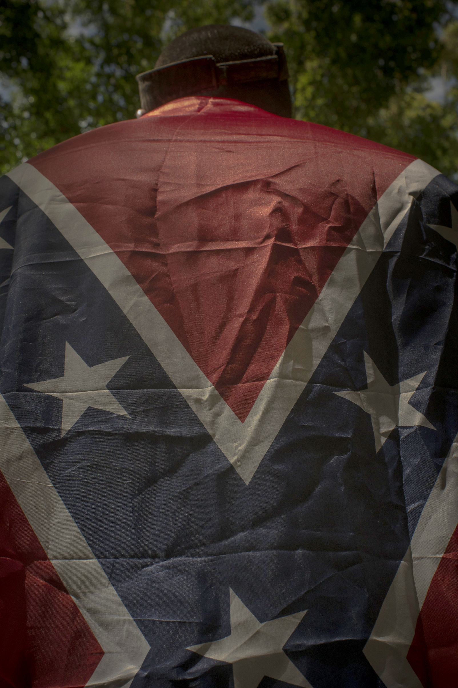 A Unite the Right protester drapes himself in a Confederate flag during a KKK rally in Charlottesville, Va., on July 8, 2017.