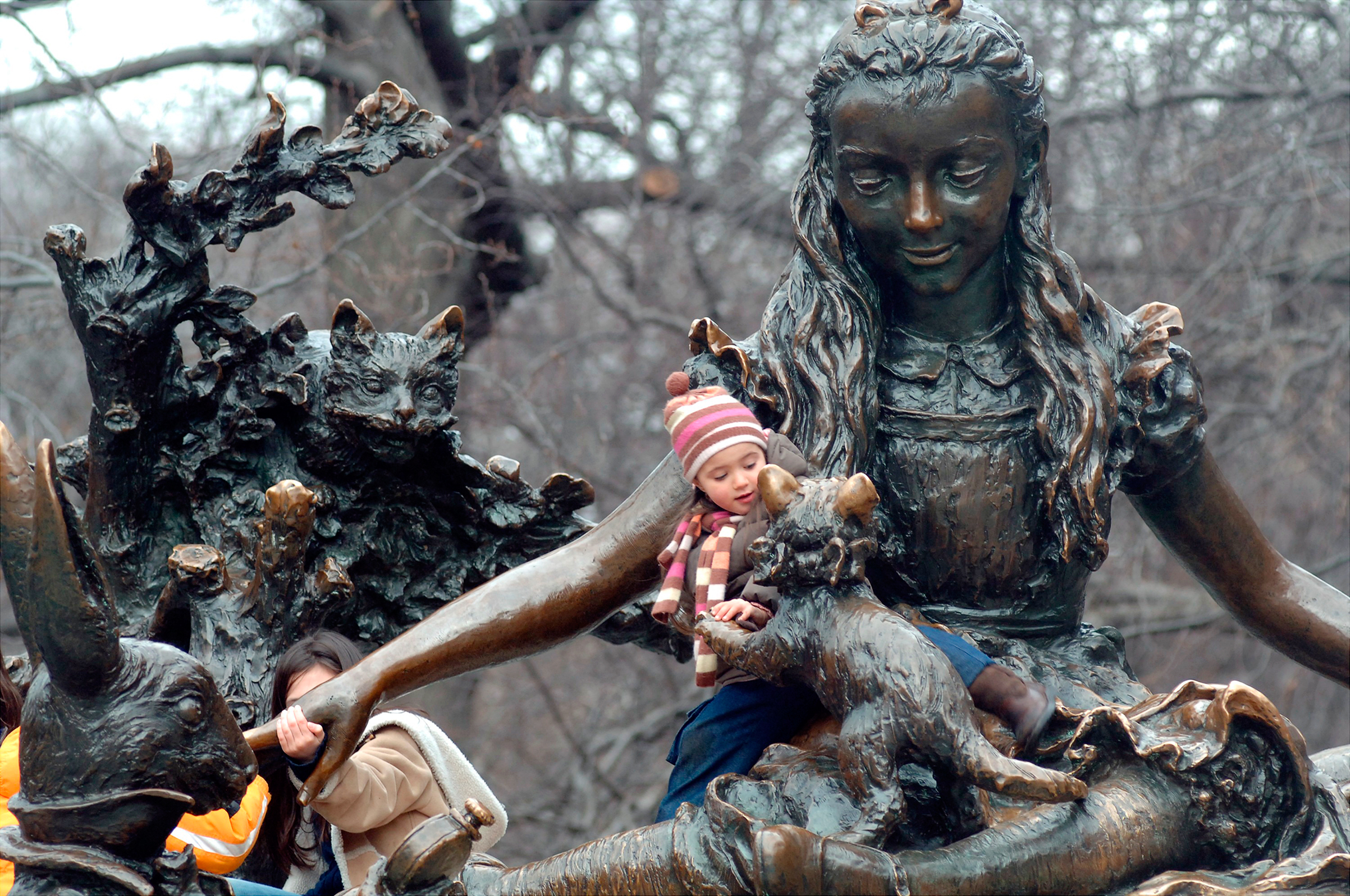 Children play on Central Park's Alice in Wonderland, one of three monuments to notable women
