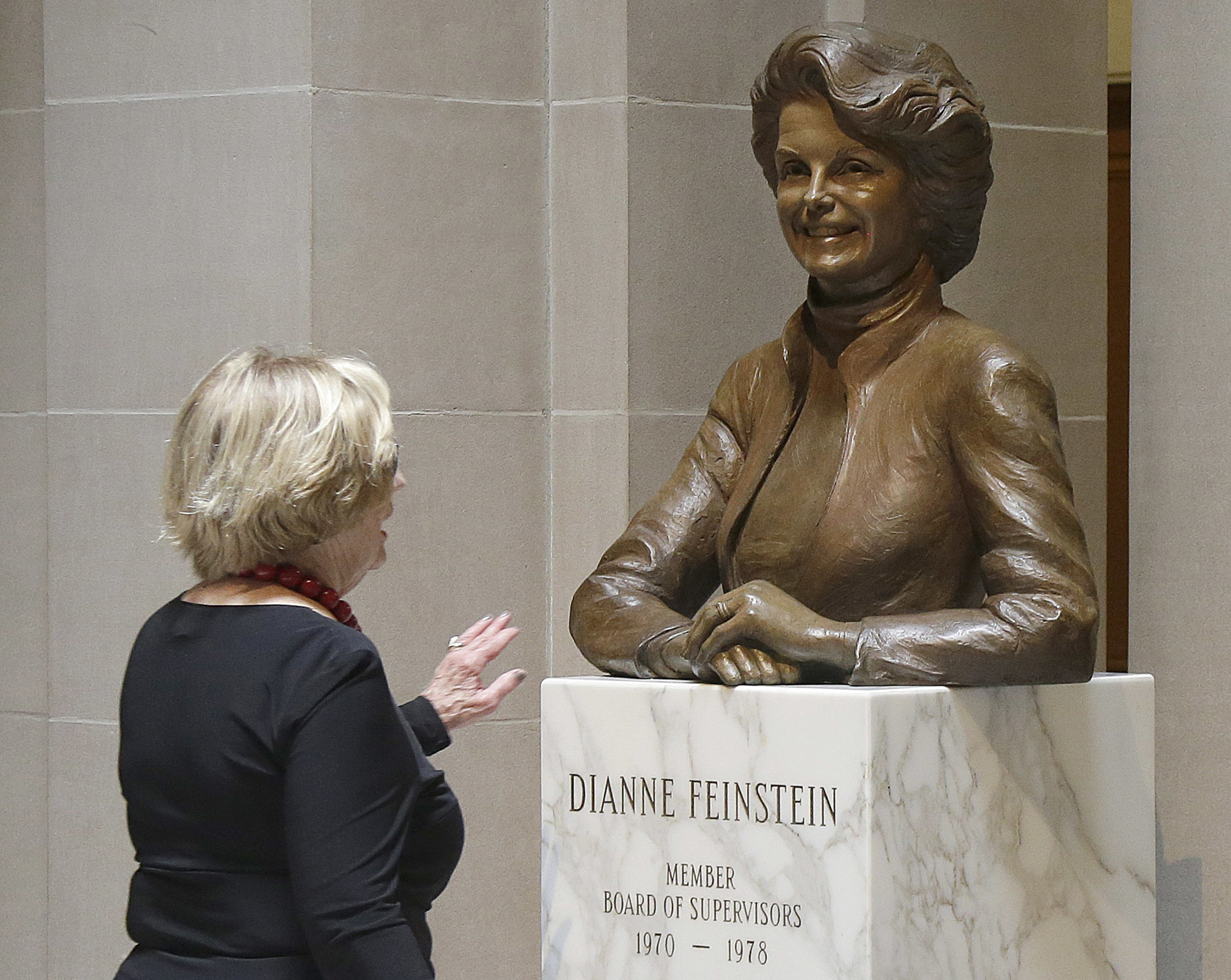 A woman walks toward the statue of Dianne Feinstein at City Hall in San Francisco, on In this June 26, 2017.
