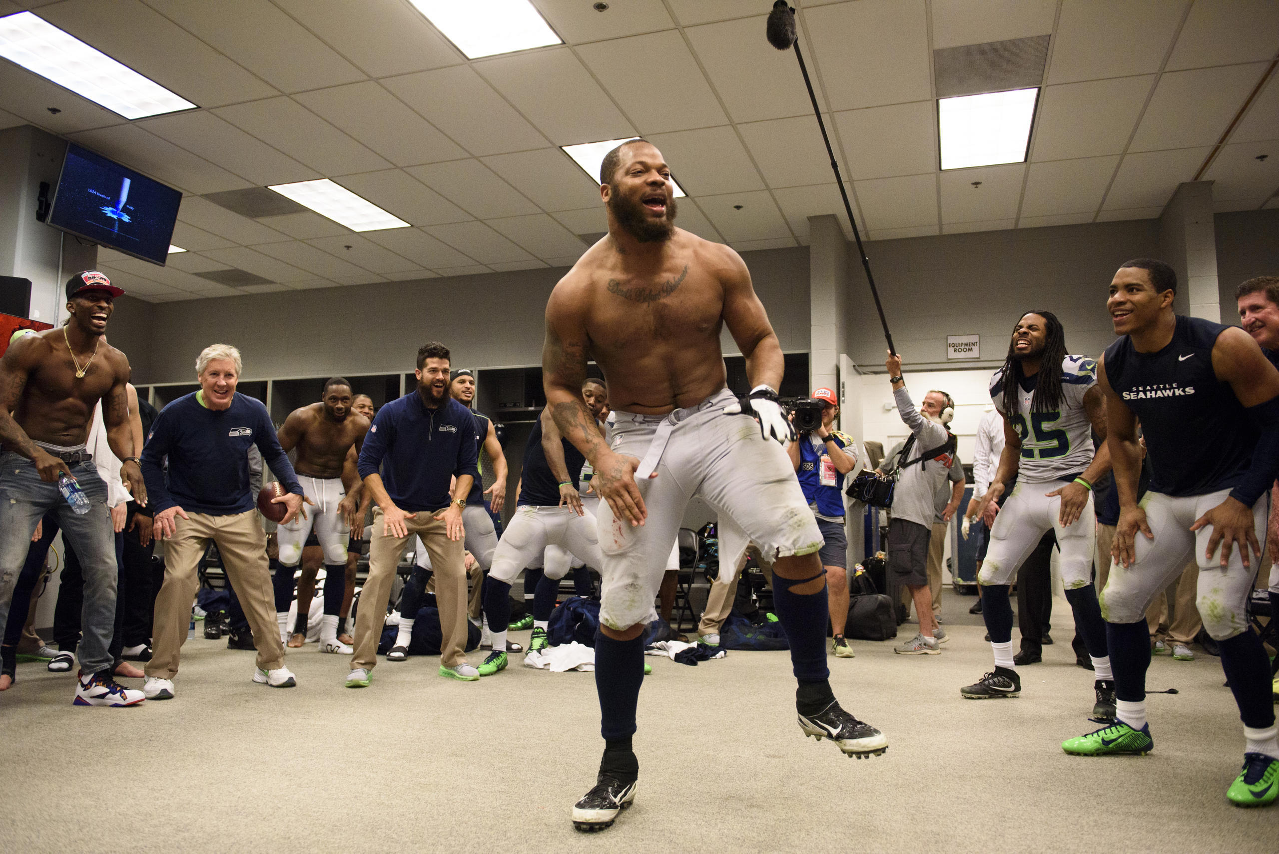 Defensive end Michael Bennett leads the team in the now-traditional post-victory dance in the locker room
