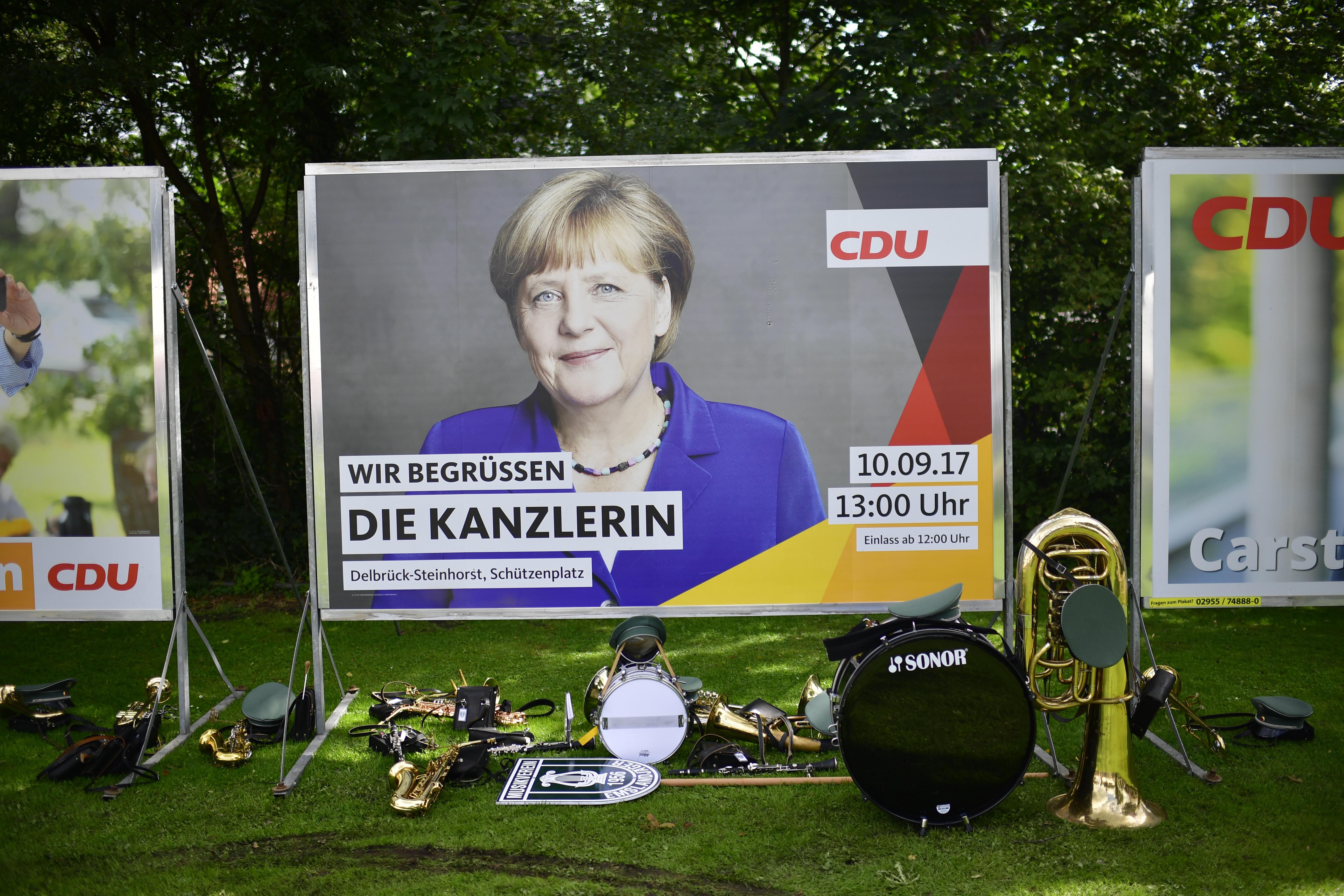 Traditional instruments stand in front of a billboard of German Chancellor and Christian Democrat (CDU) Angela Merkel.