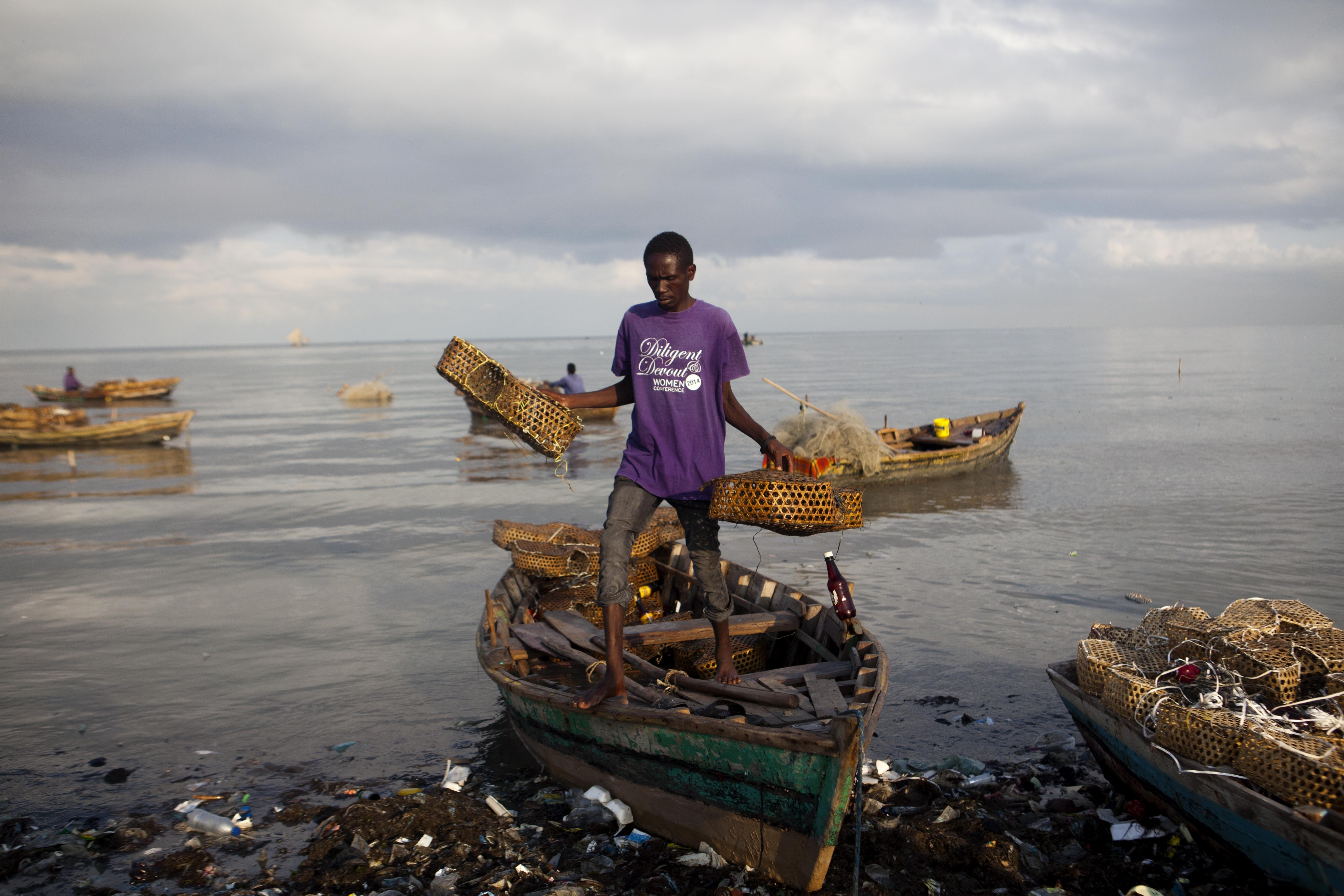 A fisherman removes equipment from his wooden boat in Port-au-Prince, Haiti, Wednesday, Sept. 6, 2017.