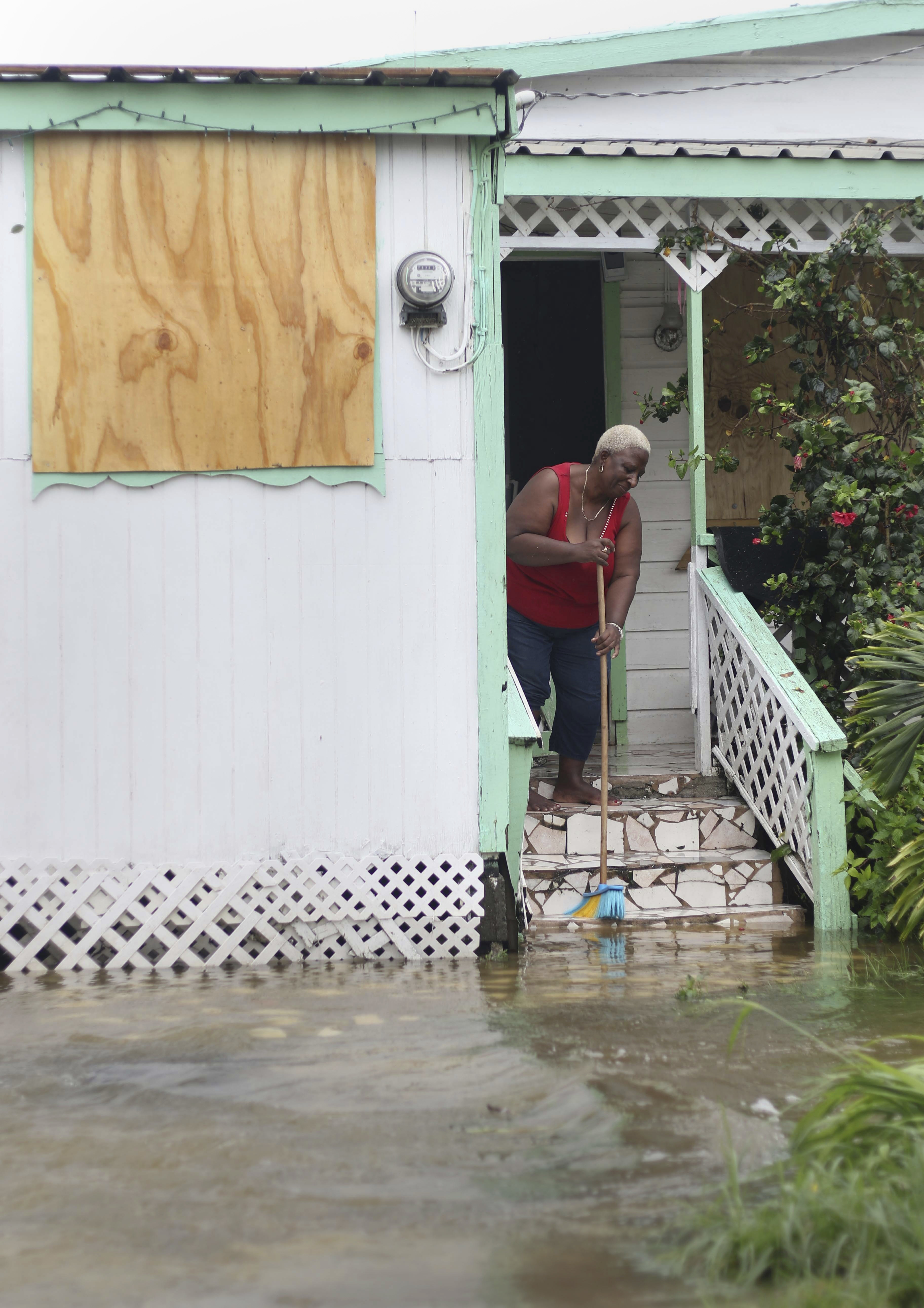 A woman pushes out floodwaters on her property after the passing of Hurricane Irma, in St. John's, Antigua and Barbuda, Wednesday, Sept. 6, 2017.