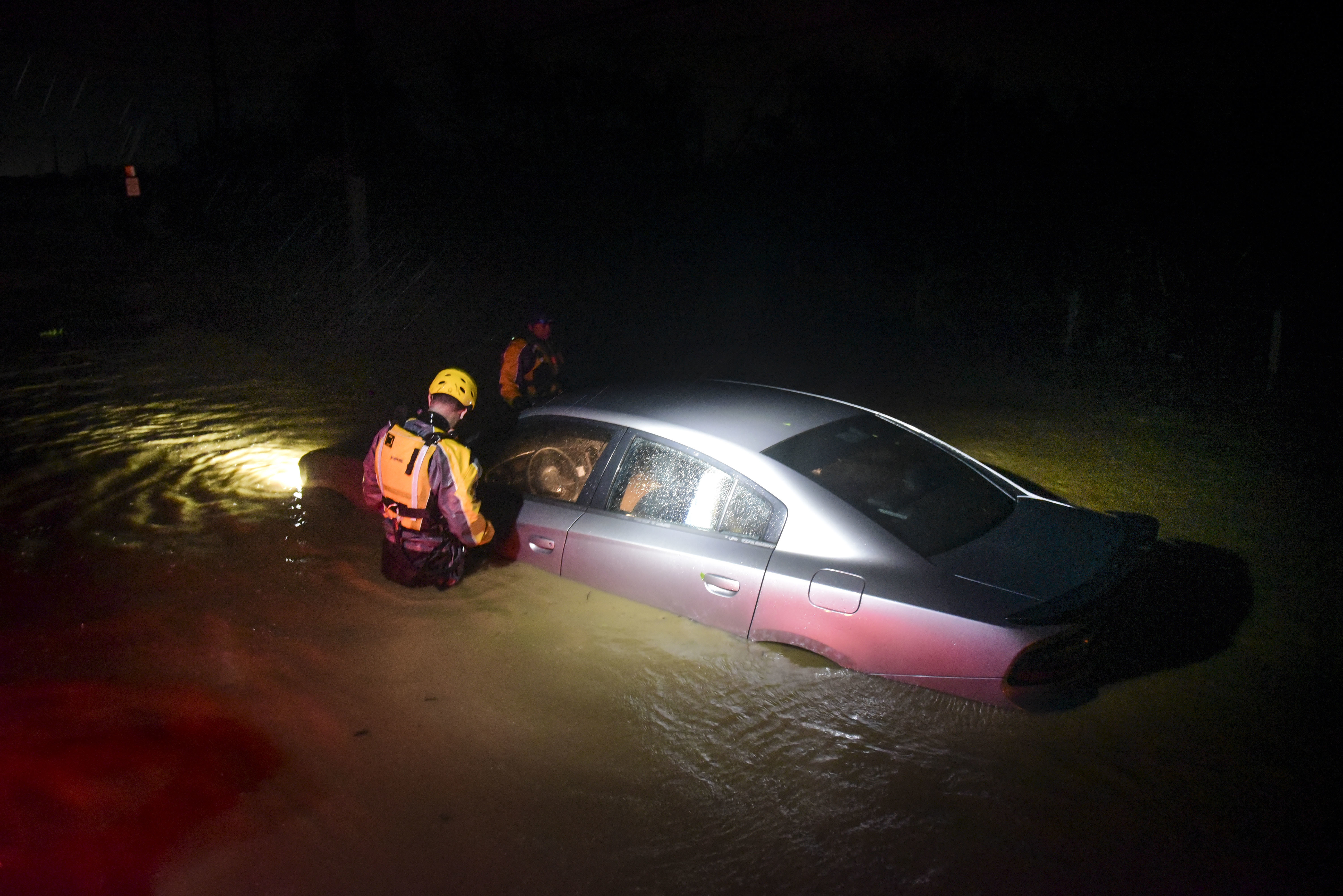 Rescue staff from the Municipal Emergency Management Agency investigate an empty flooded car in Fajardo, Puerto Rico on Wednesday, Sept. 6, 2017.