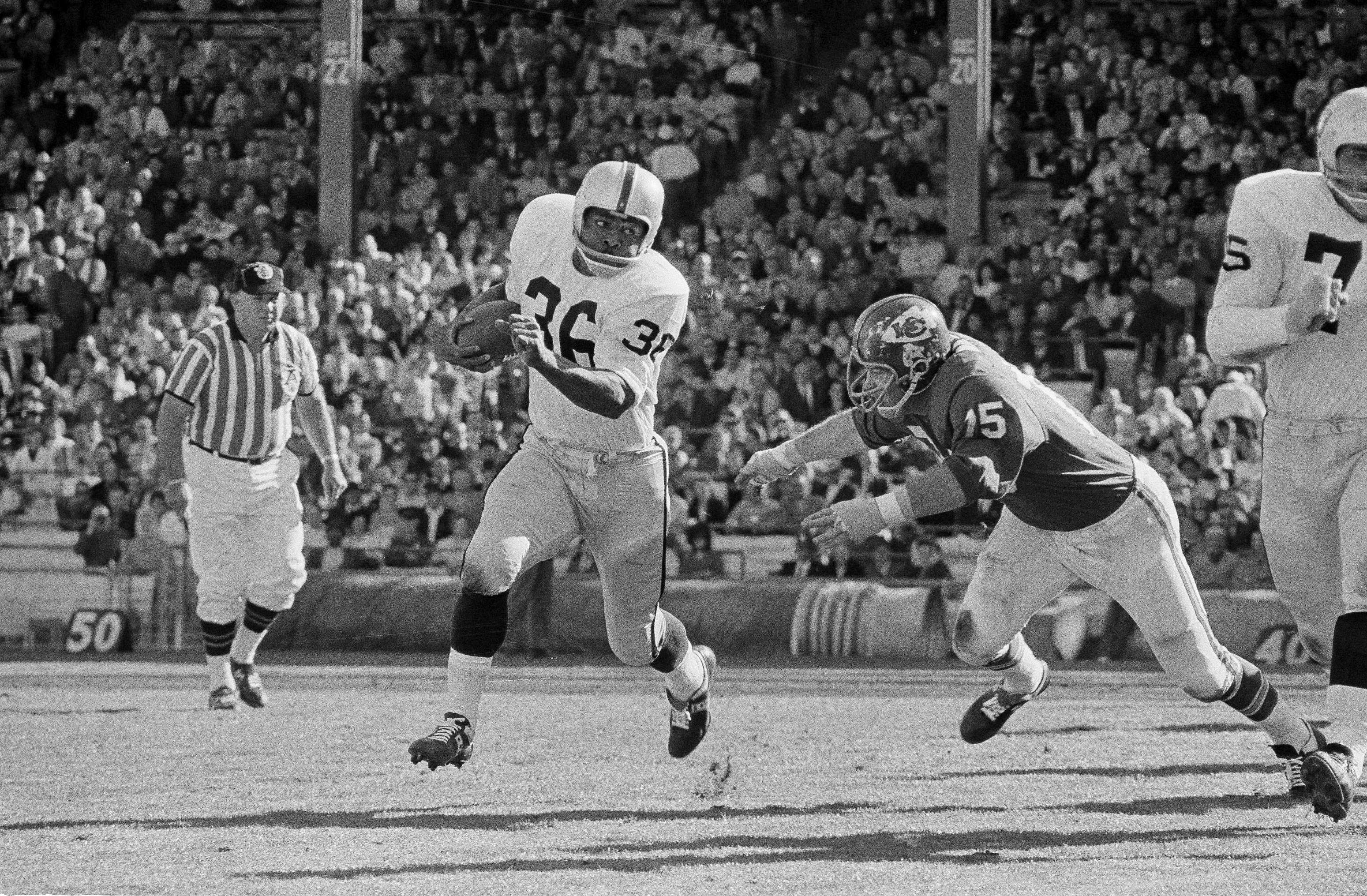 Clem Daniels (36) of the Oakland Raiders races around the right side of his line as Jerry Mays, right, of the Kansas City Chiefs moves in for the tackle, in Kansas City, Mo., Oct. 31, 1965. The Chiefs won 14-7.