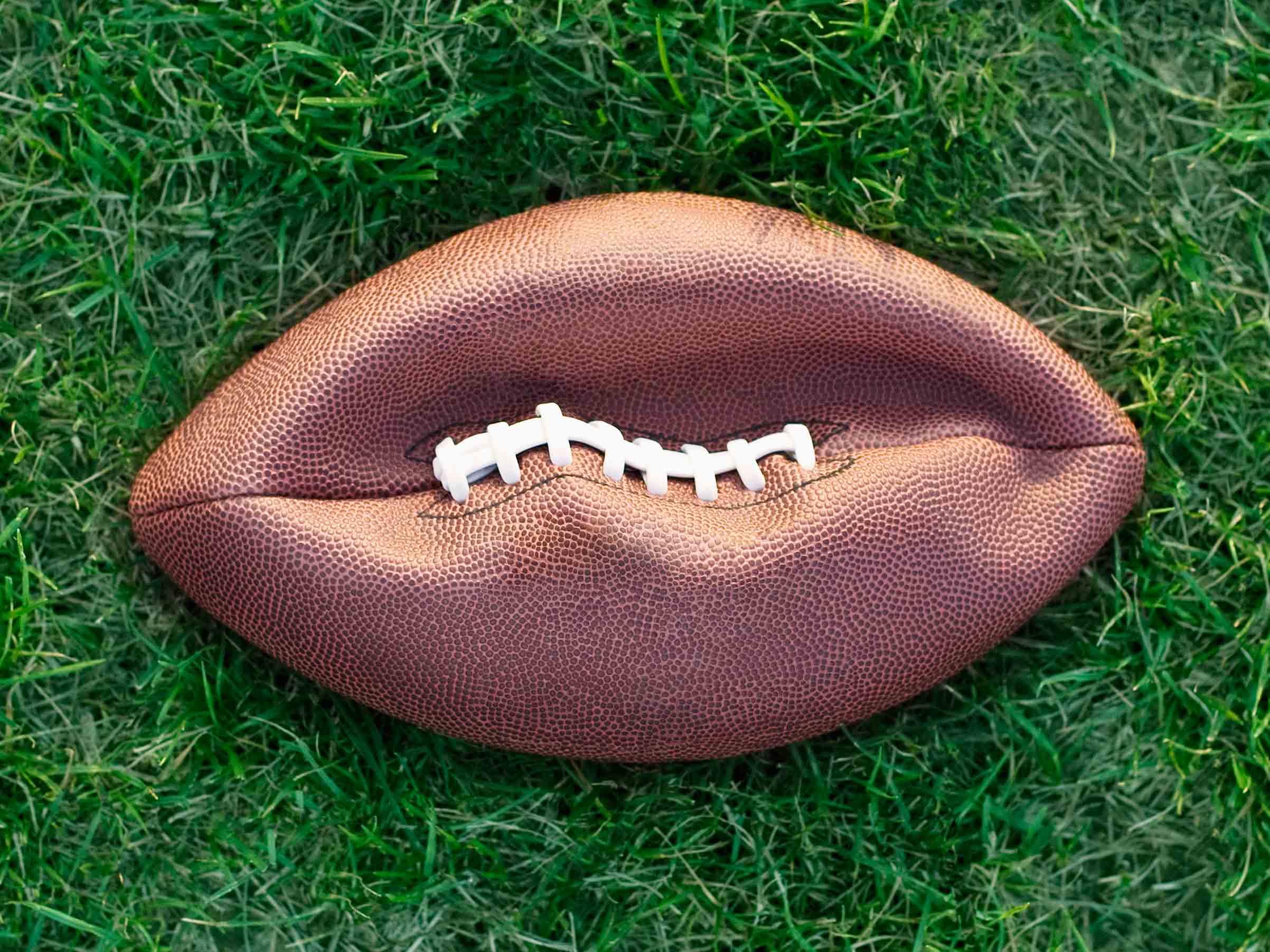 Deflated American football on grass