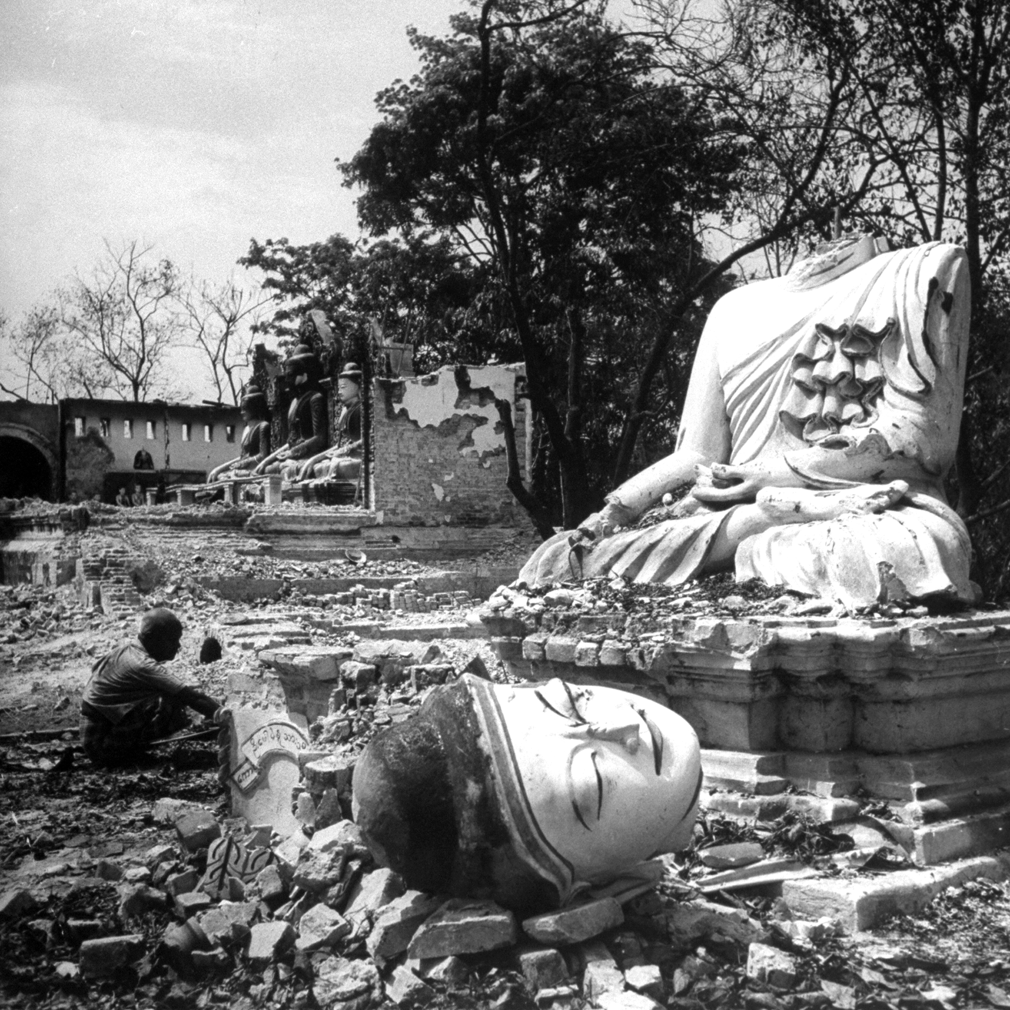 Caption from LIFE. In the rubble of a Buddhist temple destroyed by Baptist Karens, a Buddha's head lies serenely where it fell during the Battle for Bassein.