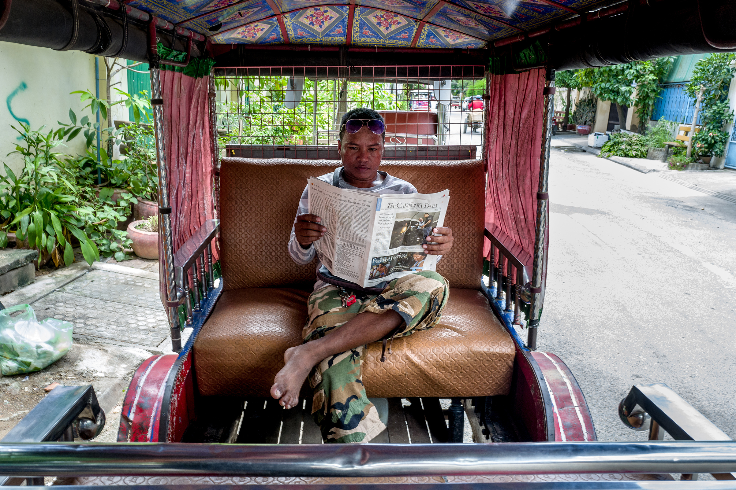 Yan Vivol, a tuk-tuk driver, reads The Cambodia Daily in Phnom Penh on Sept. 1, 2017.
