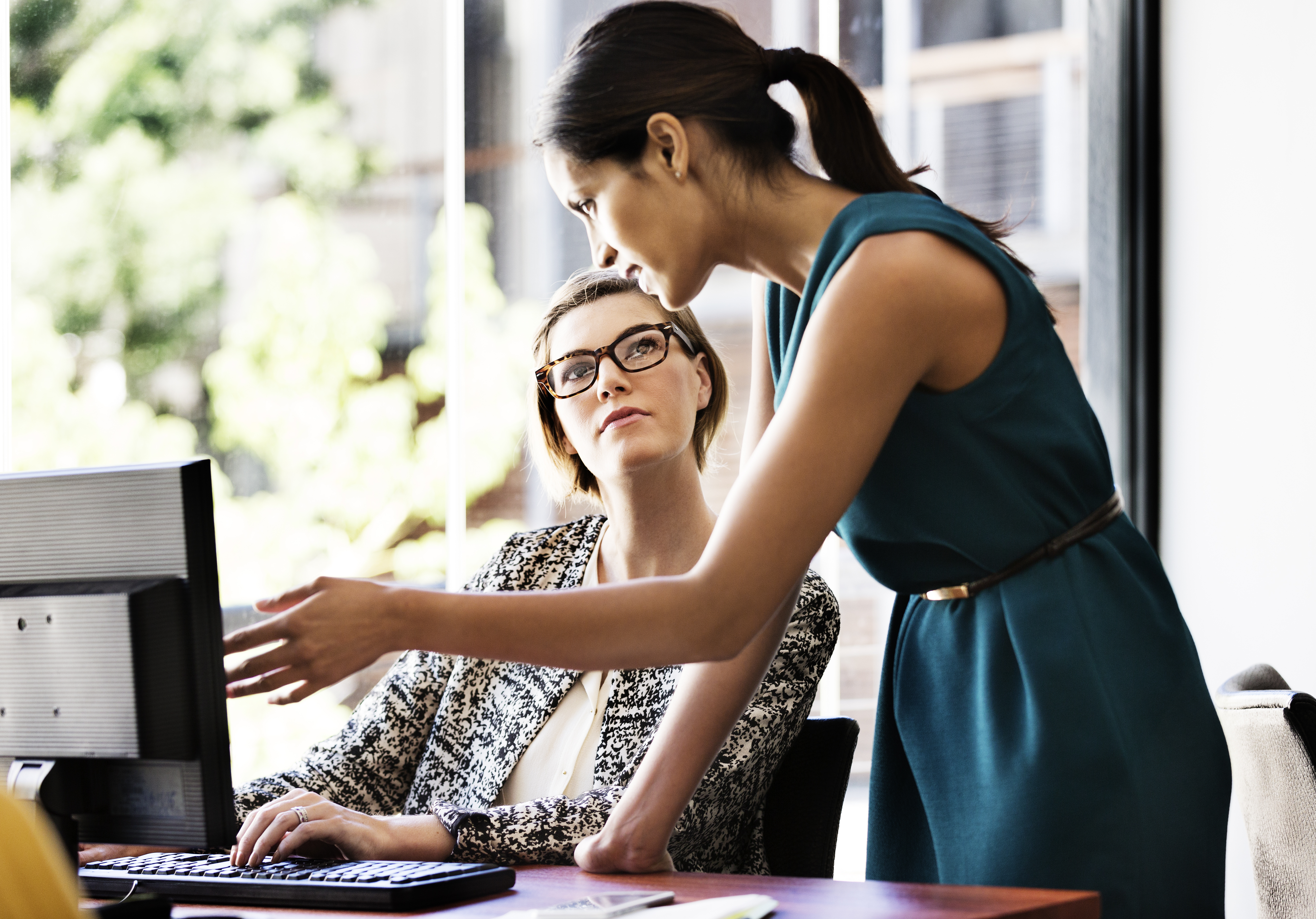 Businesswoman explaining something to female colleague over computer at desk in office