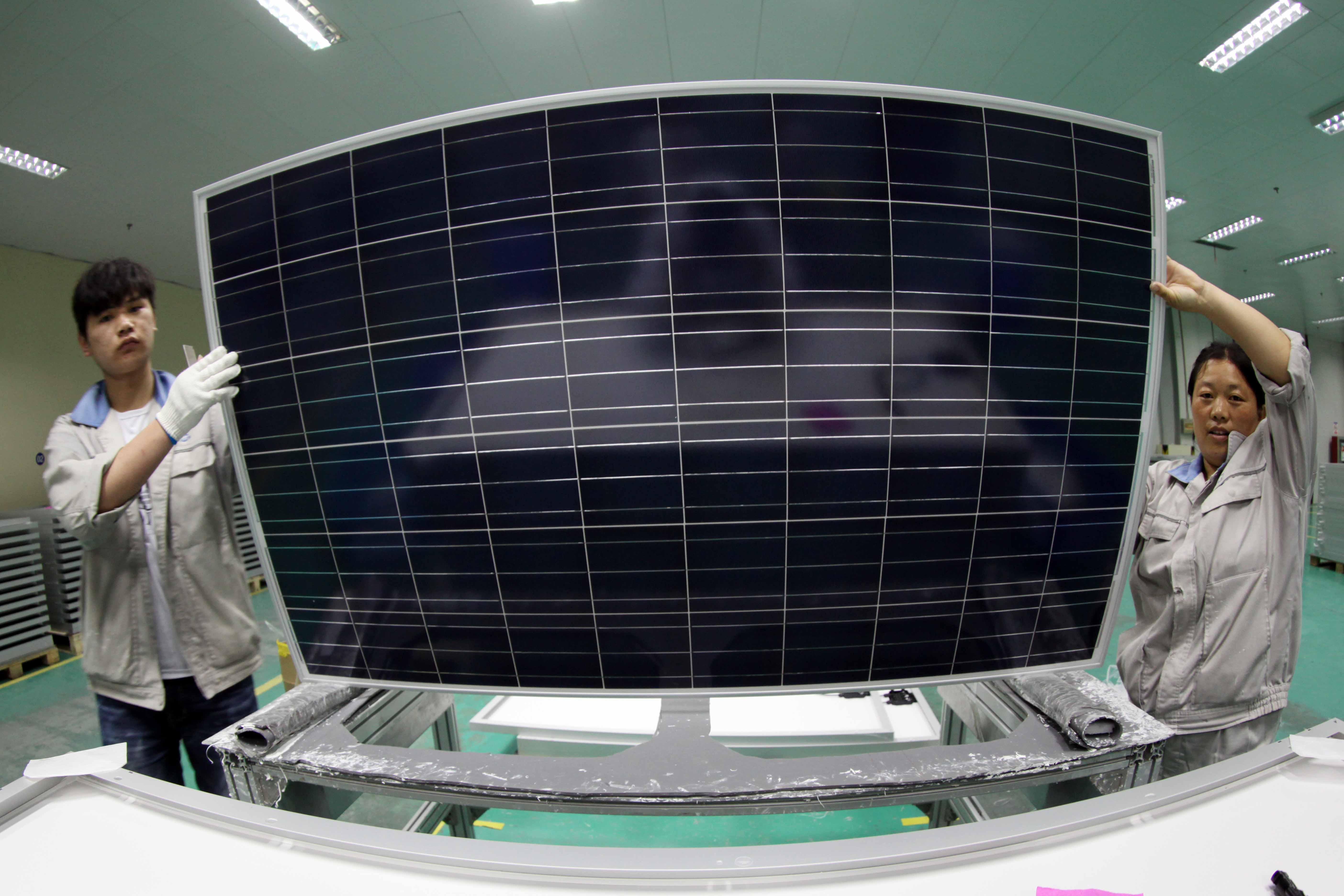 Employees work on the product line of solar panel at a solar panel factory in Lianyungang, China.