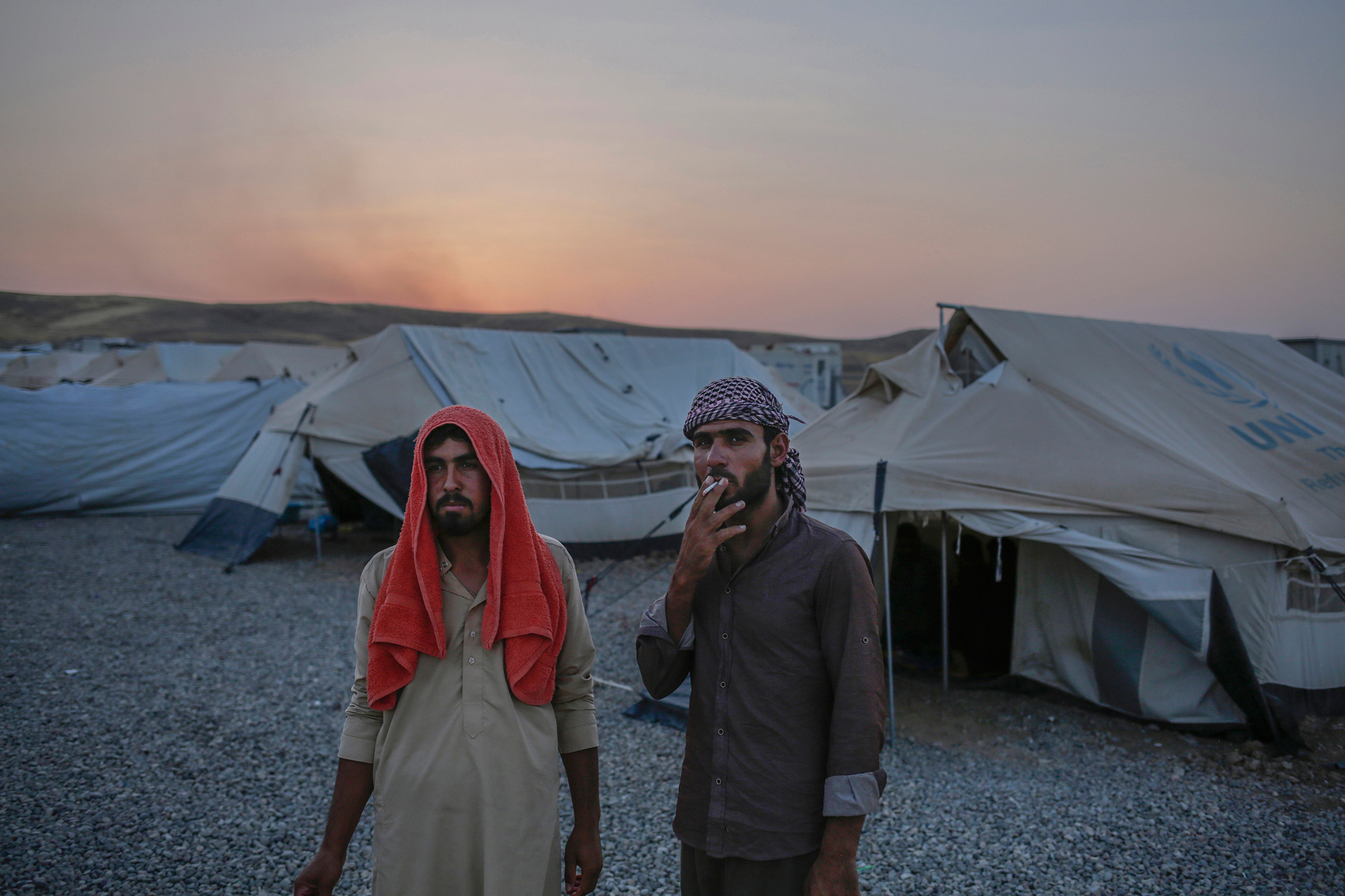 Younes Abdullah, left, and his nephew Rakan Hamid Jasim stand inside the Chamakor camp for displaced people in Northern Iraq. They both want to return to their homes in the town of Zummar, currently under Kurdish control, but Kurdish security forces don't allow them to return. The two relatives lived under Islamic State rule for almost three years.