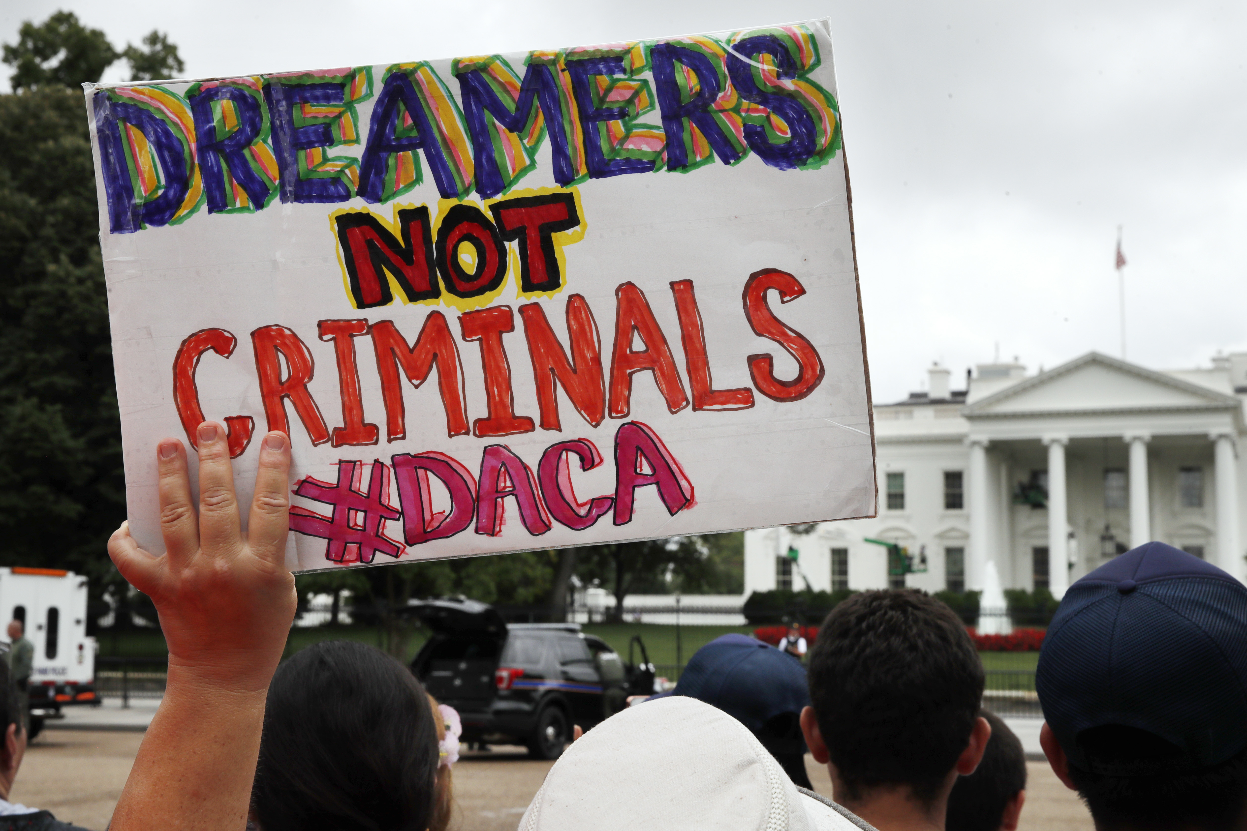 A woman holds up a signs in support of the Obama administration program known as Deferred Action for Childhood Arrivals, or DACA, during an immigration reform rally, Tuesday, Aug. 15, 2017, at the White House in Washington.