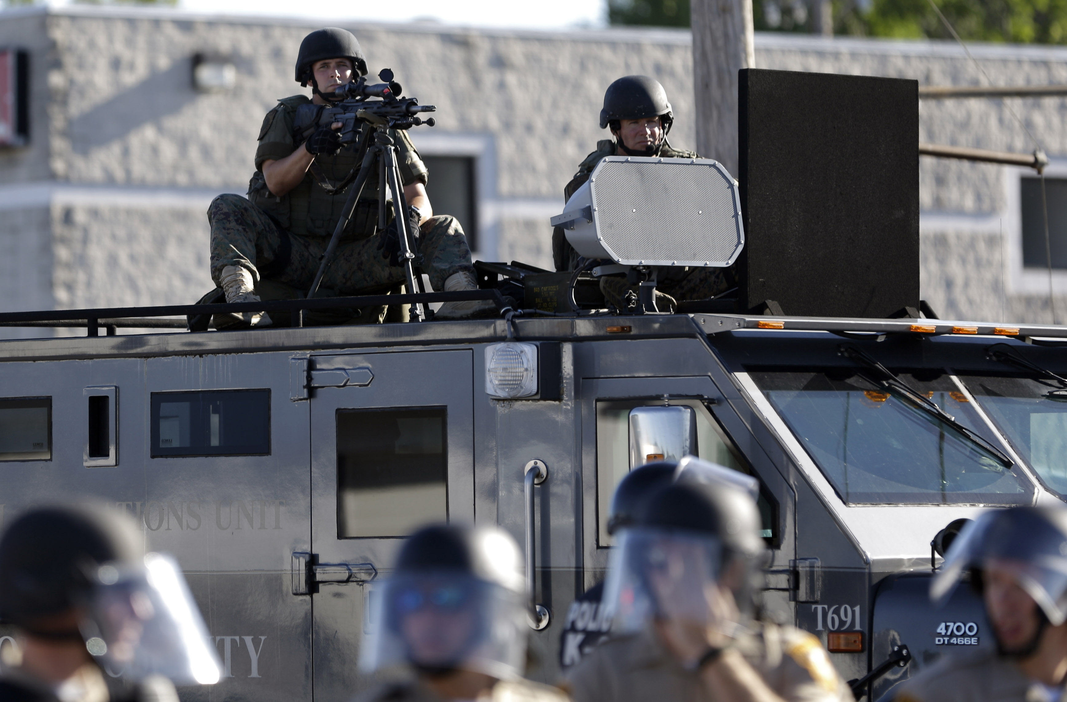 In this Aug. 9, 2014, file photo, a police tactical team moves in to disperse a group of protesters following the shooting of a young black man by a white policeman in Ferguson, Mo.
