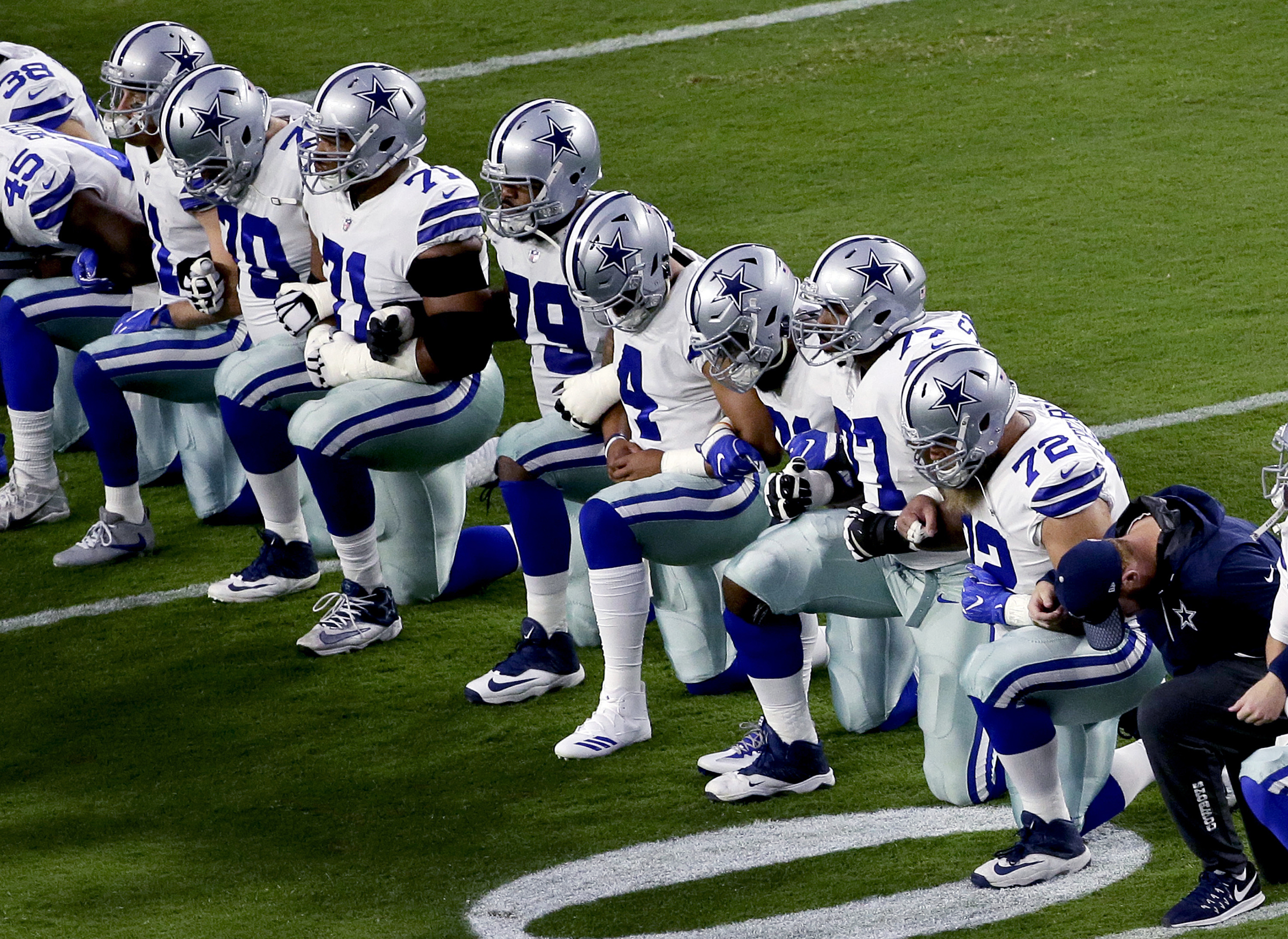 The Dallas Cowboys take a knee prior to the national anthem prior to an NFL football game against the Arizona Cardinals, Sept. 25, 2017, in Glendale, Ariz.