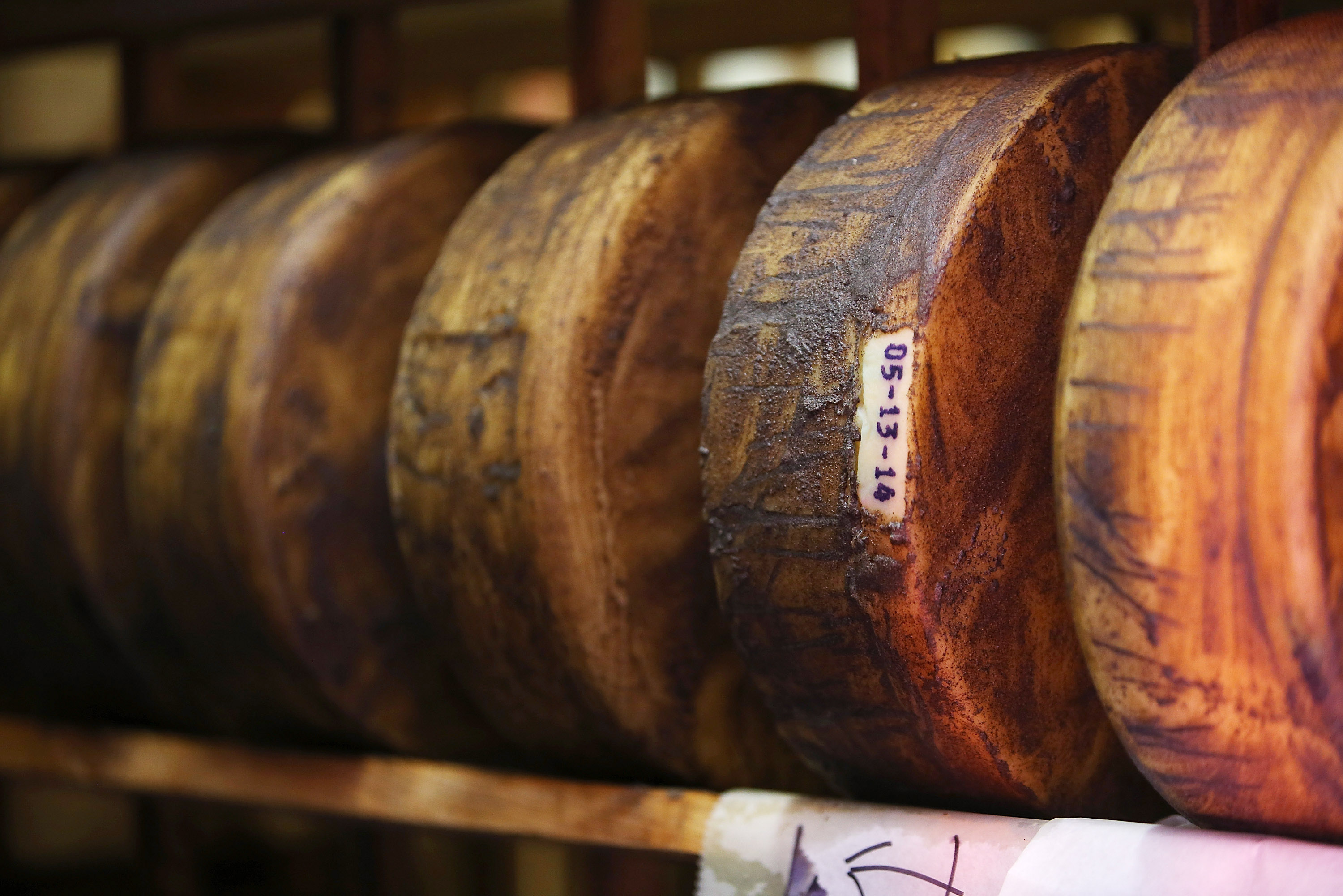 Wheels of jack cheese age on wooden racks in a cooler at Vella Cheese on June 10, 2014 in Sonoma, California.