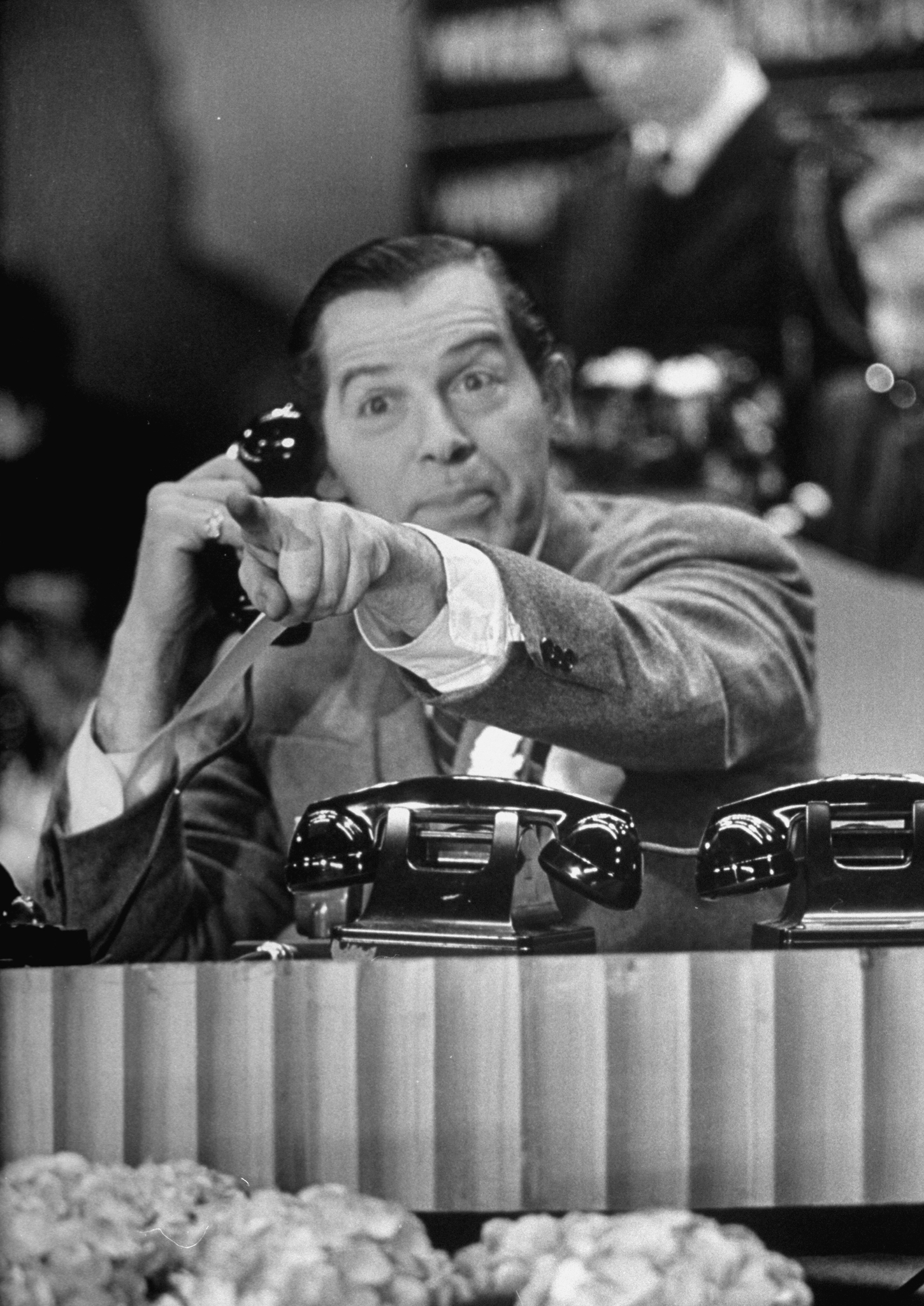 Milton Berle taking a call from a viewer while hosting a fundraiser for the Damon Runyon Memorial Cancer Fund on N.B.C's broadcasting channel.
