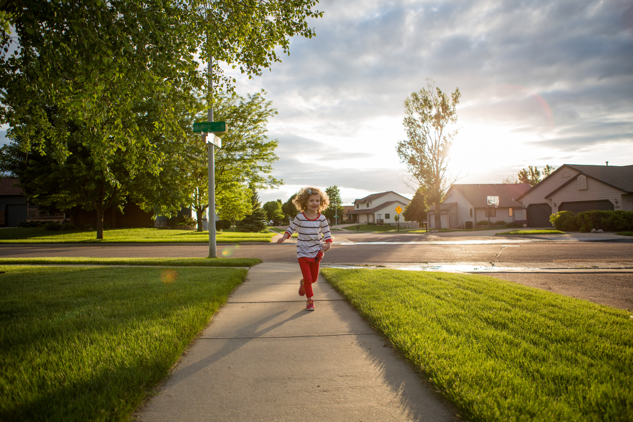 Little girl runs down a sidewalk in a neighborhood on a sunny summer evening.