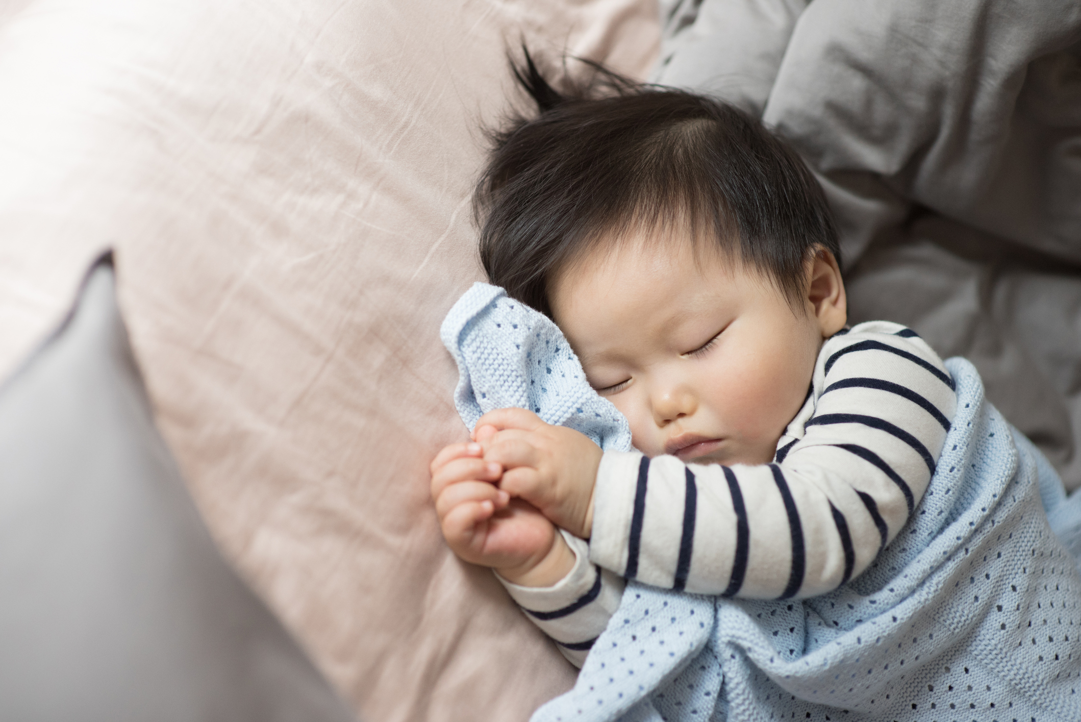 11 months old baby boy sleeping on bed
