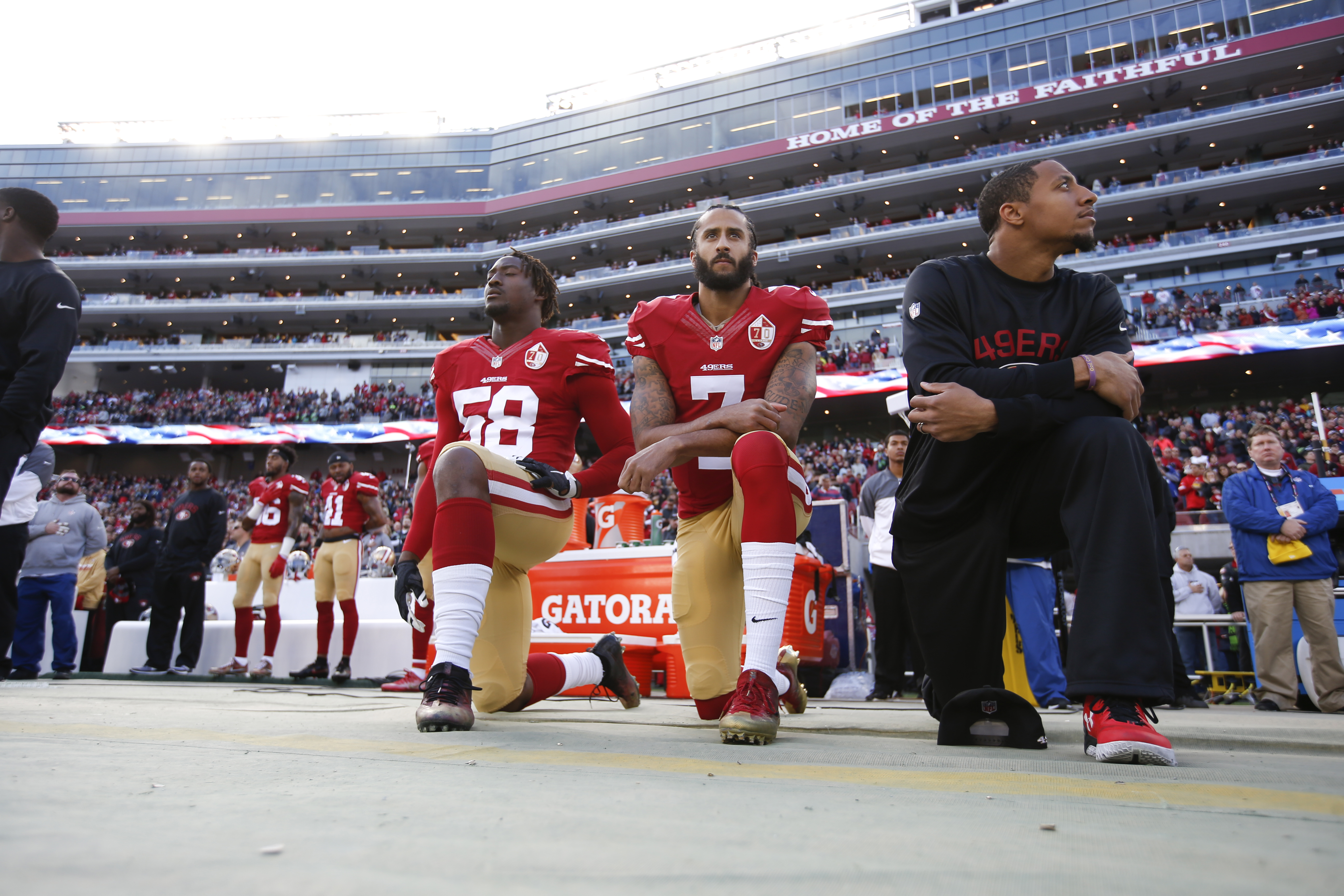 SANTA CLARA, CA - JANUARY 1: Eli Harold #58, Colin Kaepernick #7 and Eric Reid #35 of the San Francisco 49ers kneel on the sideline, during the anthem, prior to the game against the Seattle Seahawks at Levi Stadium on January 1, 2017 in Santa Clara, California. The Seahawks defeated the 49ers 25-23.