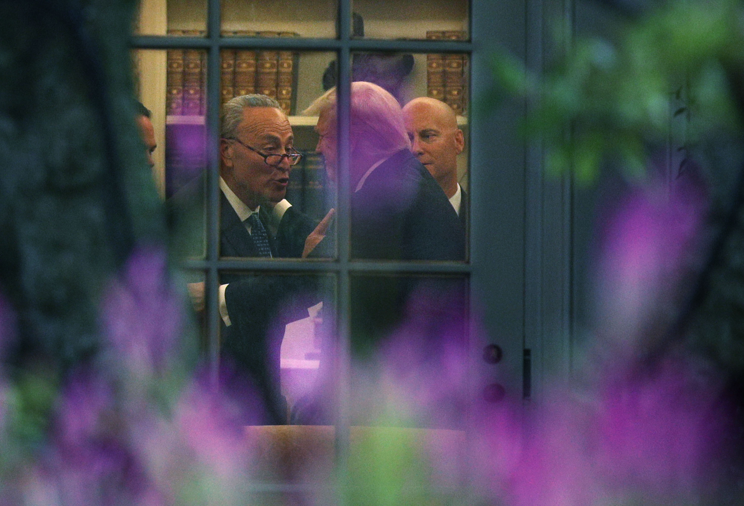 U.S. Senate Minority Leader Chuck Schumer (D-NY) (L) makes a point to President Donald Trump in the Oval Office prior to his departure from the White House September 6, 2017 in Washington, D.C.