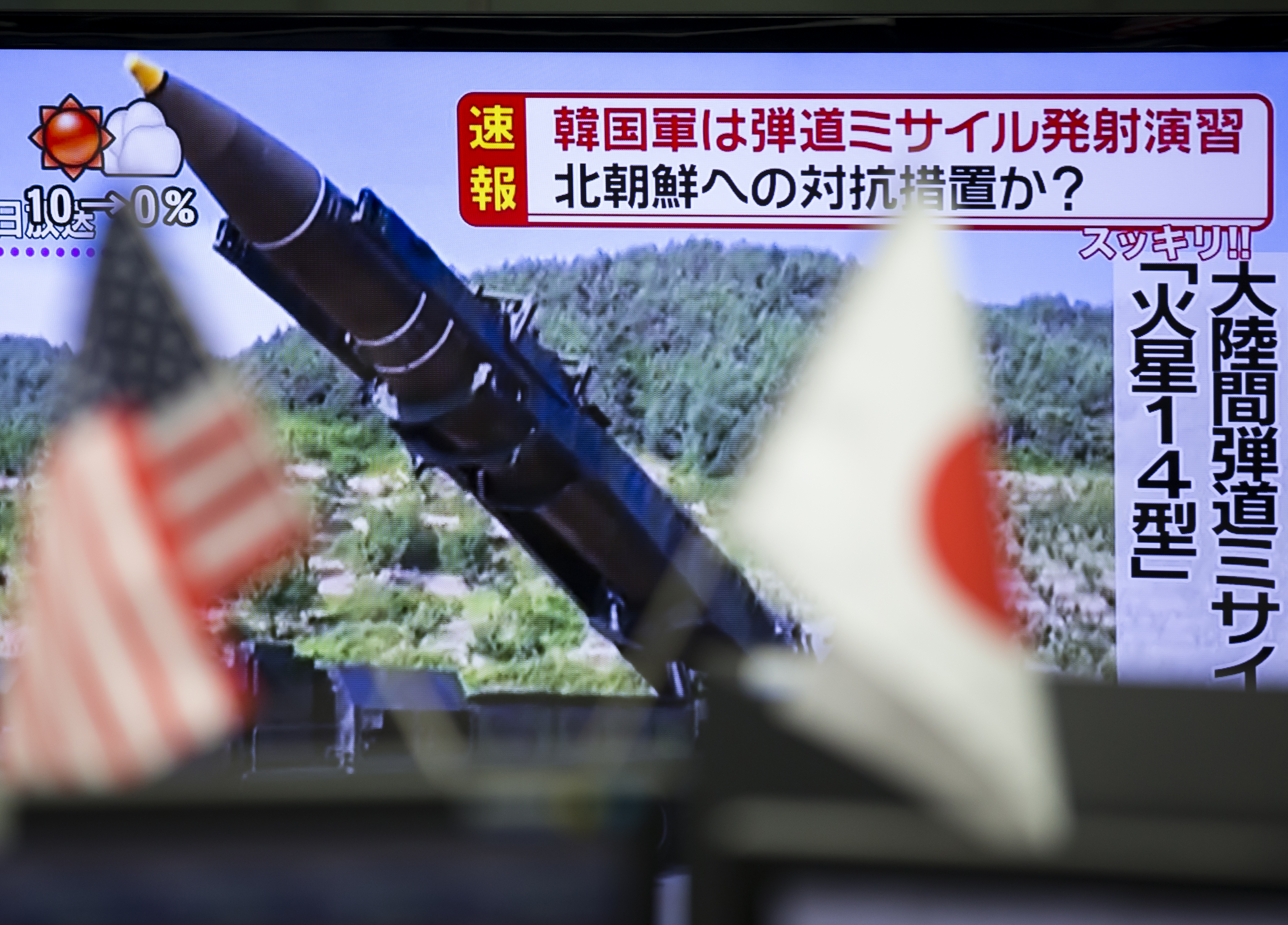 American and Japanese flags are displayed in front of a monitor showing a news broadcast of North Korea's missile launch at a foreign exchange brokerage in Tokyo, Japan, on Friday, Sept. 15, 2015.