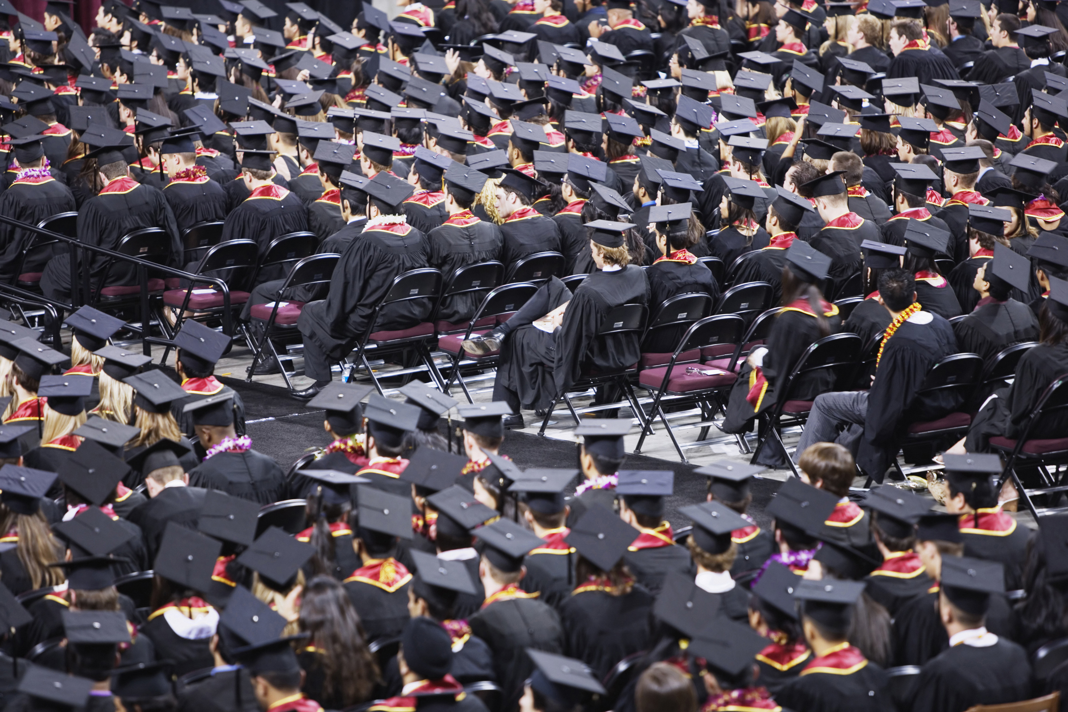 High angle view of rows of seated students in caps and gowns during a graduation ceremony in a indoor auditorium, University of Southern California, Los Angeles, California.
