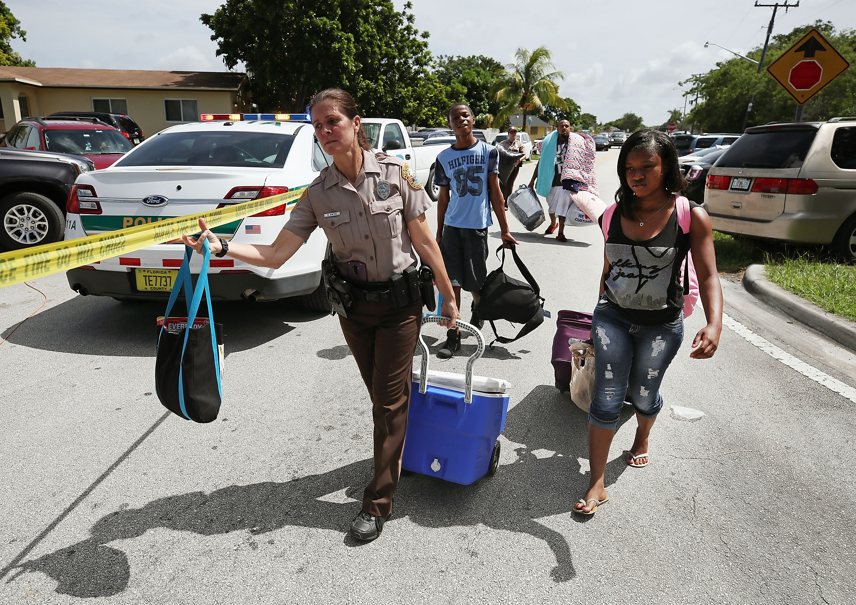 Officer Kerensa Smith with the Miami Dade Police Department helps evacuees move to a bus to take them to a shelter as Hurricane Irma approaches Miami on September 8, 2017.