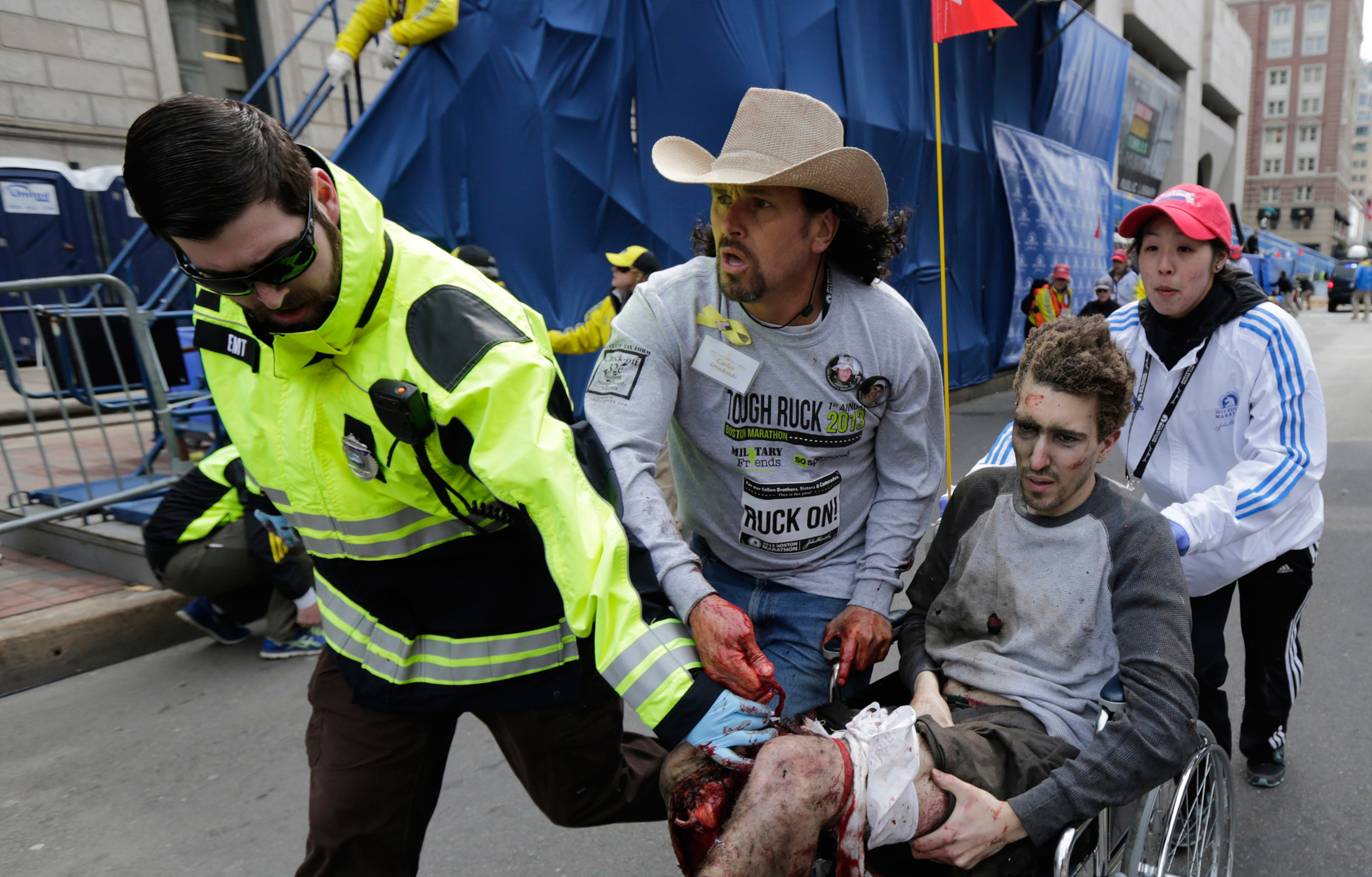 Bauman is helped by EMT Paul Mitchell, left, Carlos Arredondo, center, and Devin Wang, right, after he was injured in one of two explosions near the finish line of the Boston Marathon on April 15, 2013.