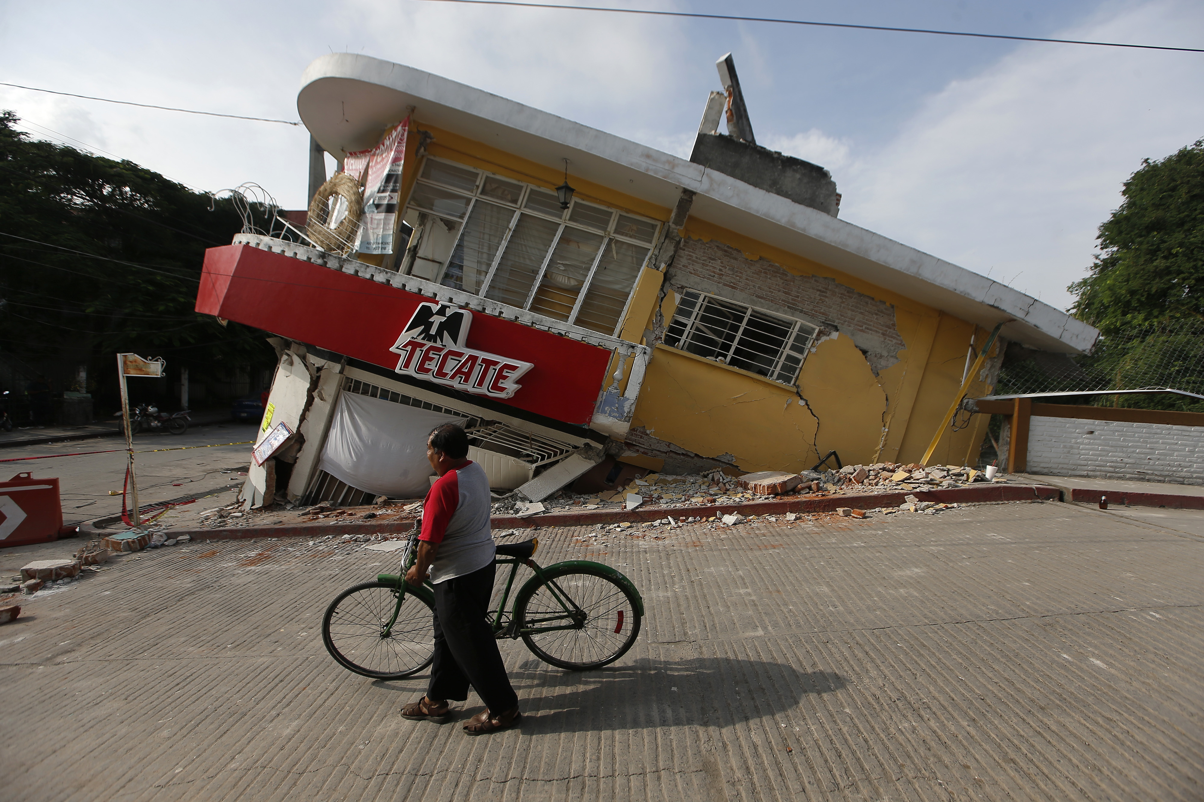 A man walks his bike past a building felled by a 7.1 earthquake, in Jojutla, Morelos state, Mexico, Wednesday, Sept. 20, 2017.