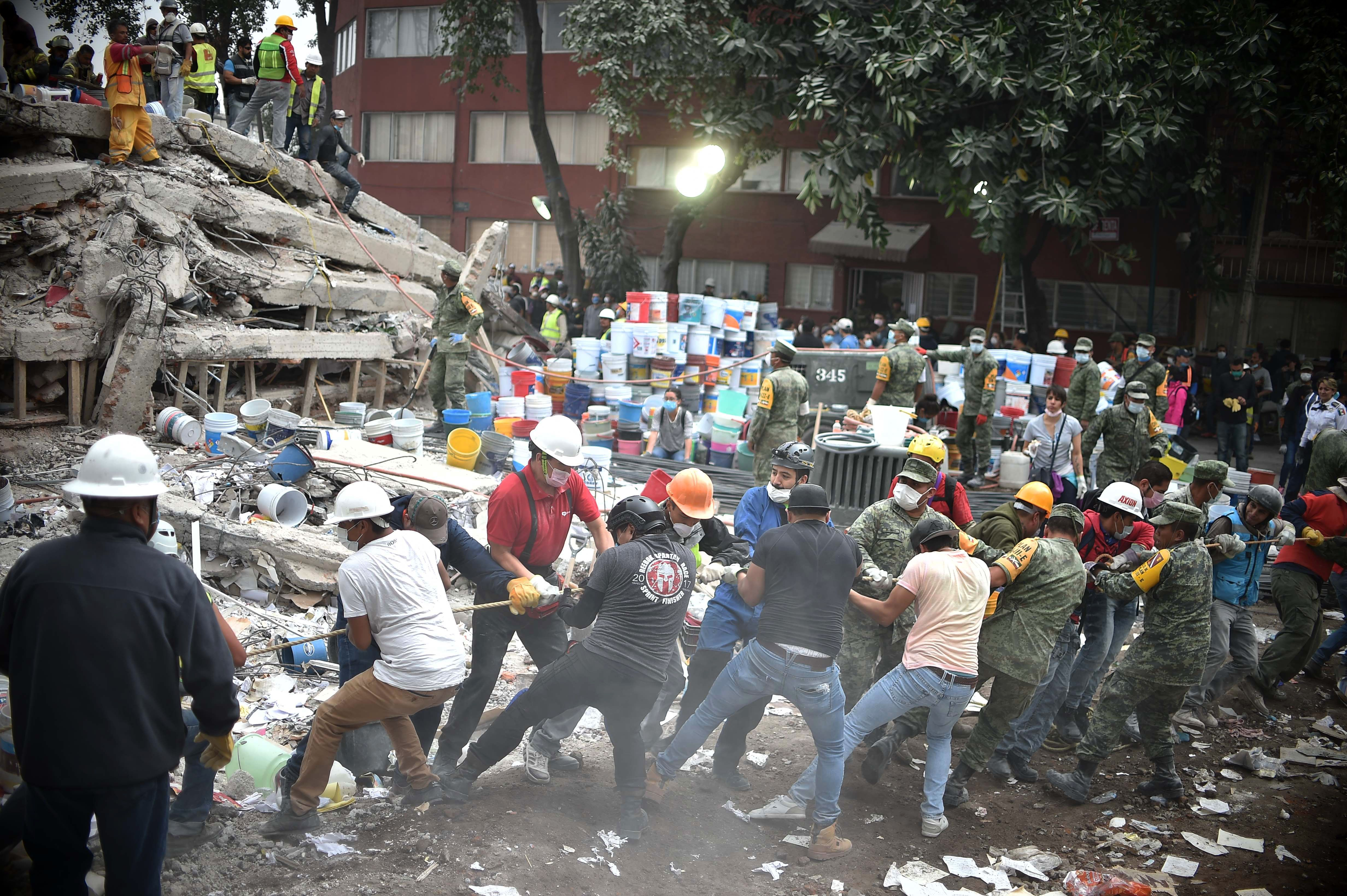 Rescuers, firefighters, policemen, soldiers and volunteers search for survivors in a flattened building in Mexico City on Sept. 20, 2017, one day after the earthquake struck the capital.