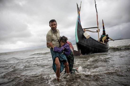 A Rohingya man helps an elderly woman reach the Bangladeshi shore from the boat in which they escaped Myanmar