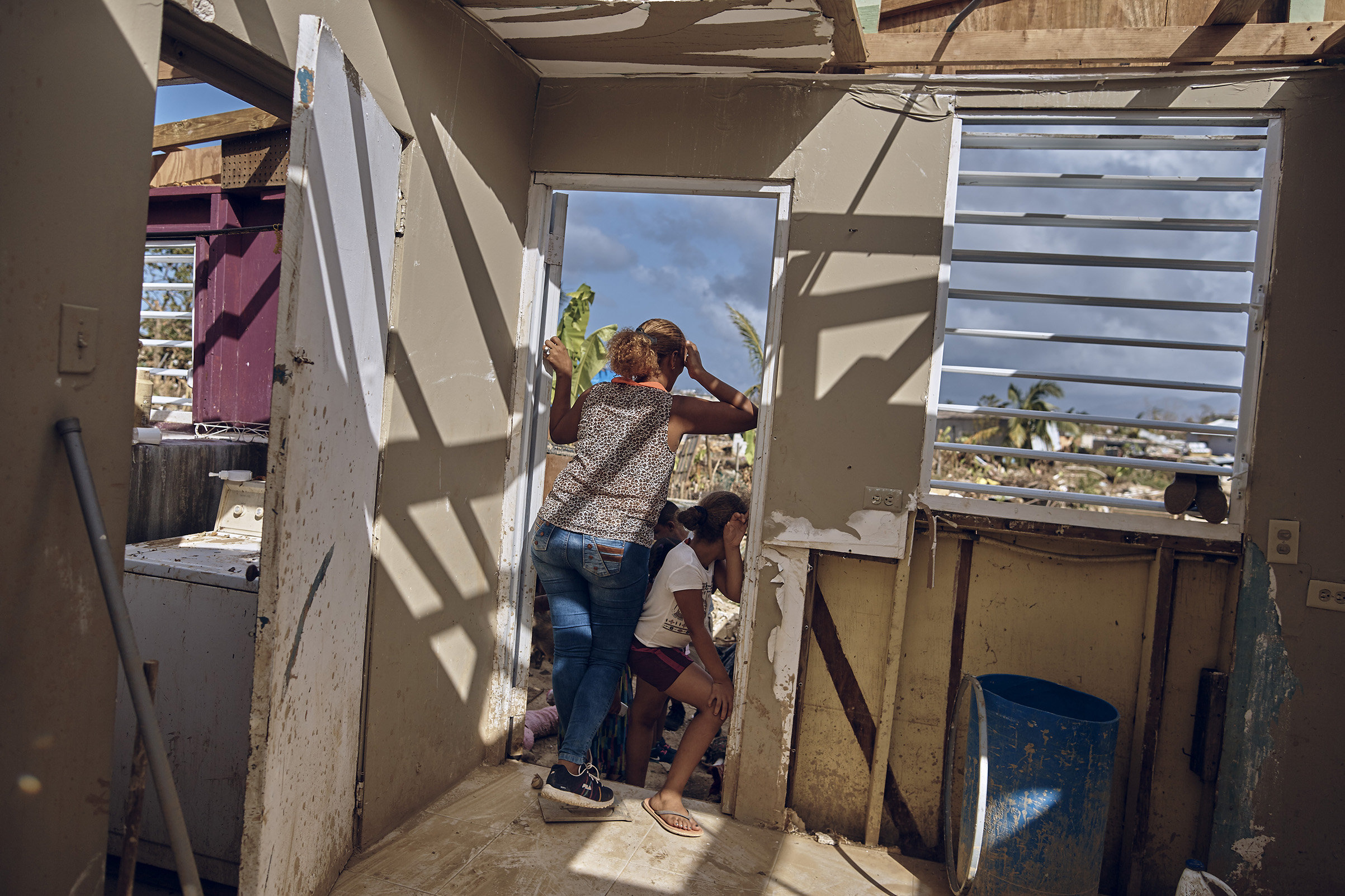 A woman look out from her damaged house in San Isidro, Puerto Rico on Sept. 28, 2017.