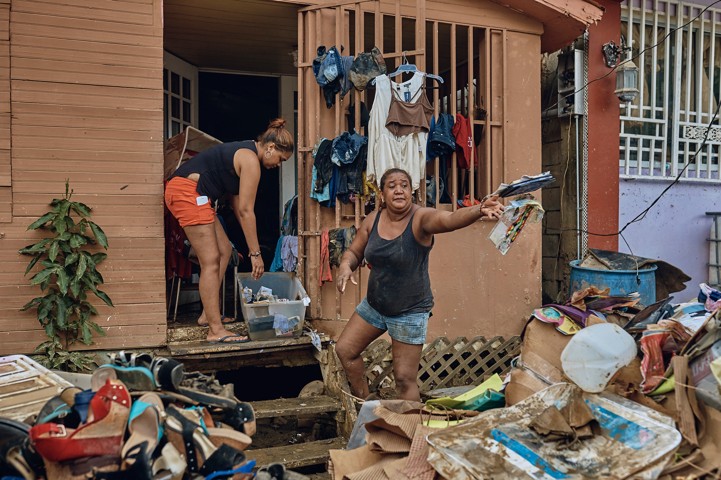 Belkis, 42, right, and her daughter remove damaged belongings from their flooded home in San Isidro, Puerto Rico, on Sept. 28, 2017.