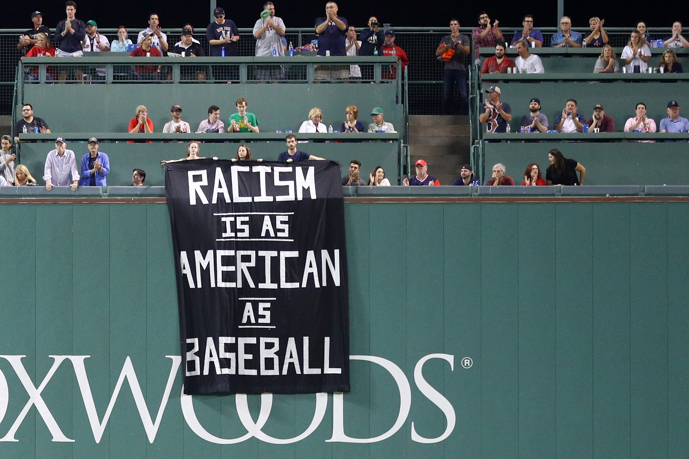 A banner with the message  Racism is as American as baseball  is draped over the Green Monster during the fourth inning of the game between the Boston Red Sox and the Oakland Athletics at Fenway Park on September 13, 2017 in Boston.