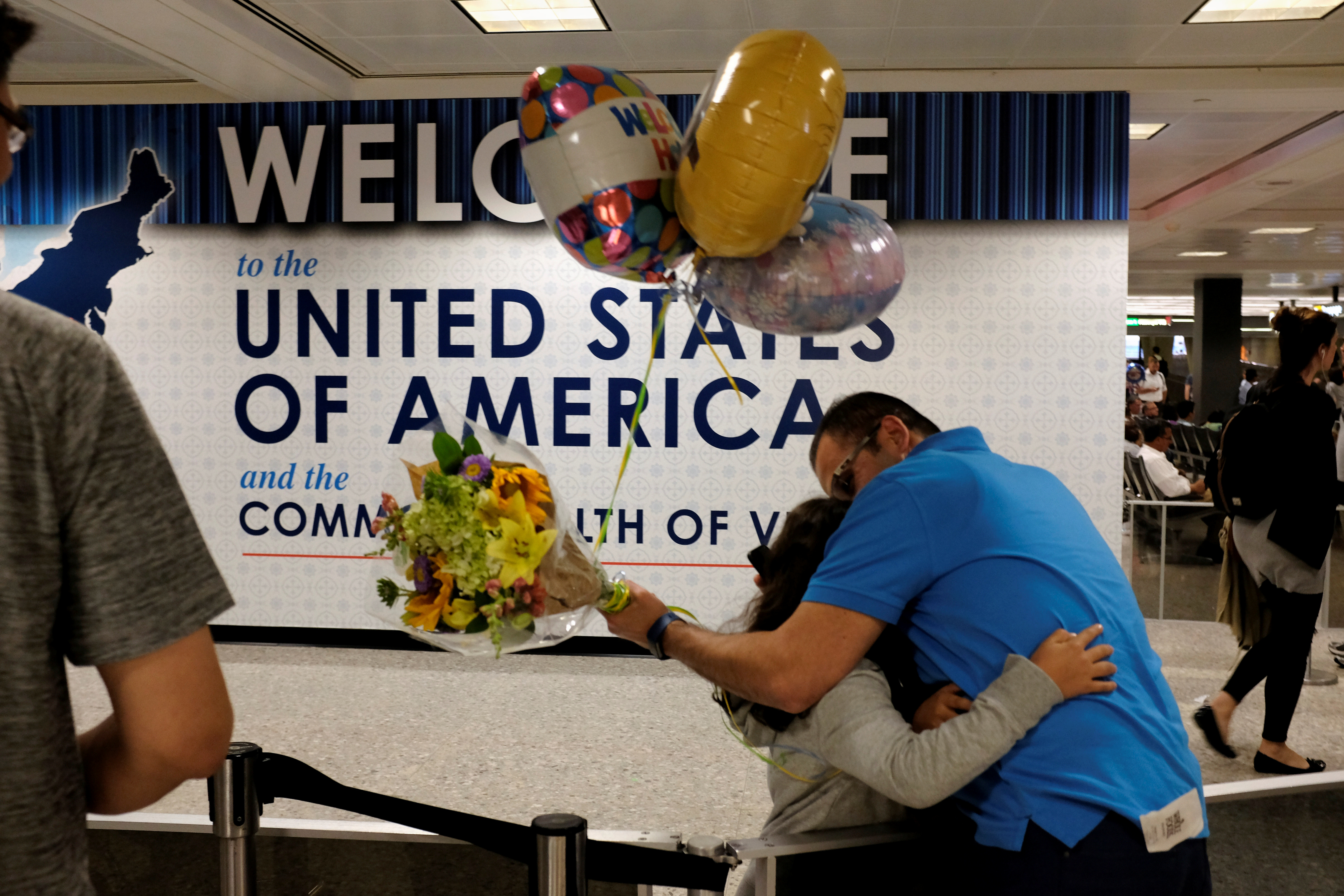 Ahmed Khalil, an Egyptian national residing in the United States, hugs his daughters as they arrive at Washington Dulles International Airport after the Trump administration's travel ban was allowed back into effect on June 29, 2017.