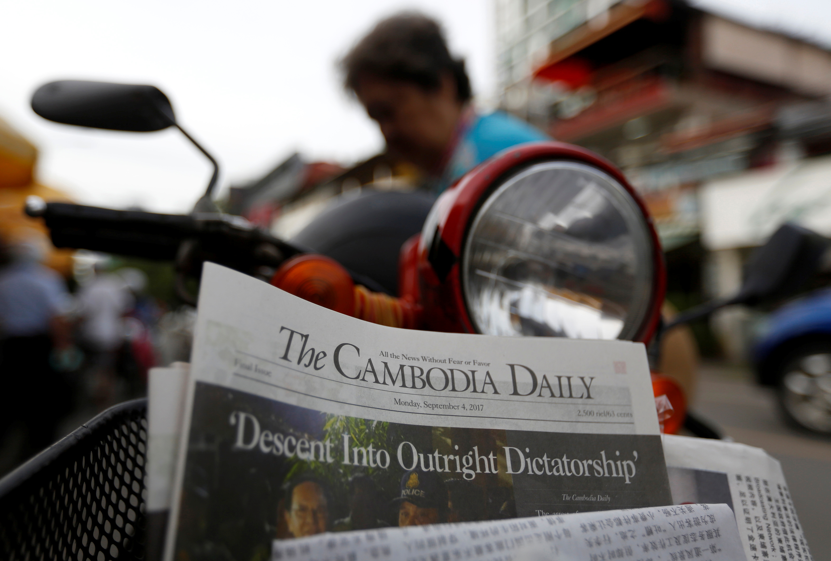 A woman buys the final issue of The Cambodia Daily newspaper at a store along a street in Phnom Penh, Cambodia, Sept. 4, 2017.