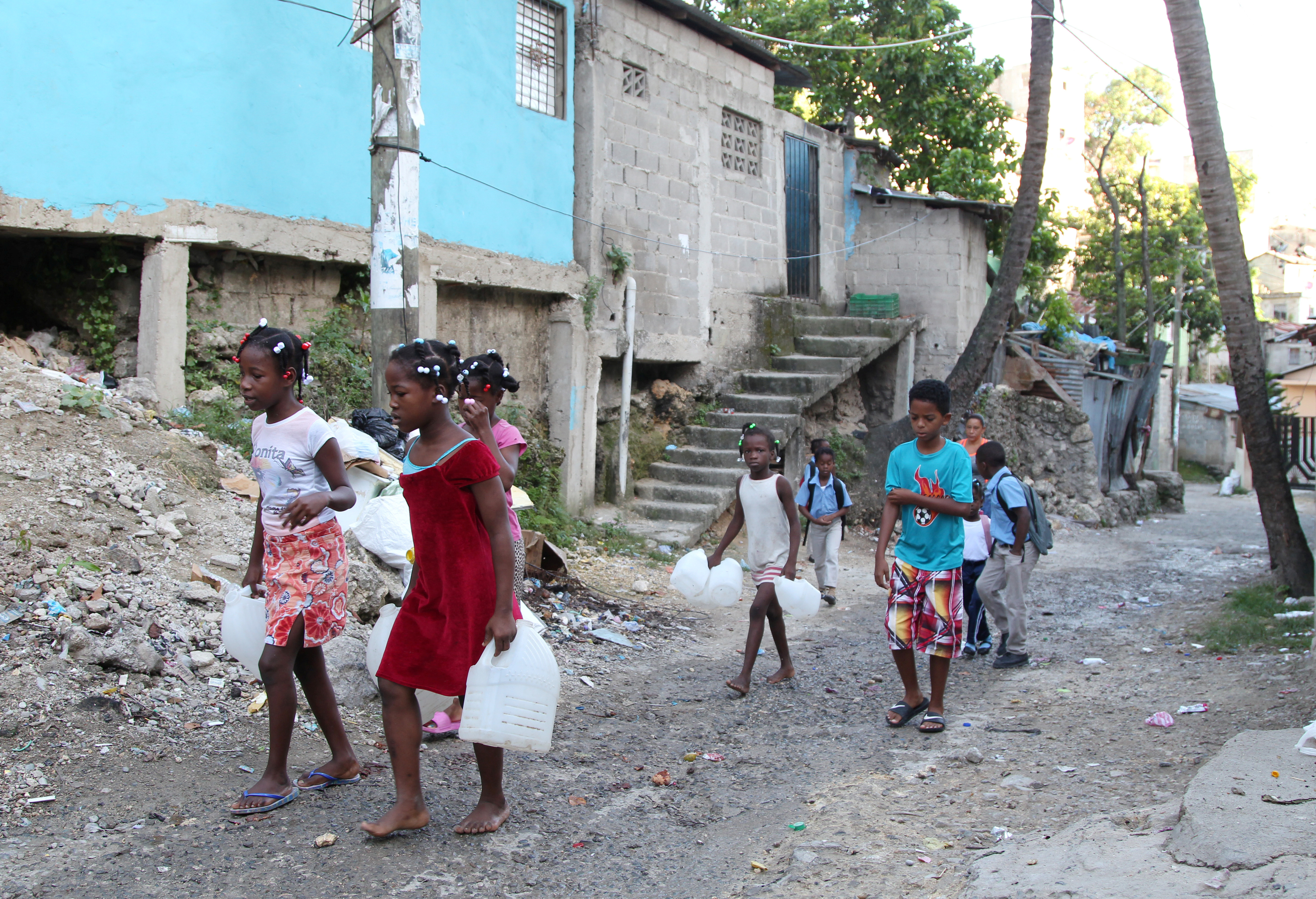 Children carry containers for water as Hurricane Irma slammed across islands in the northern Caribbean on Wednesday in Santo Domingo, Dominican Republic.