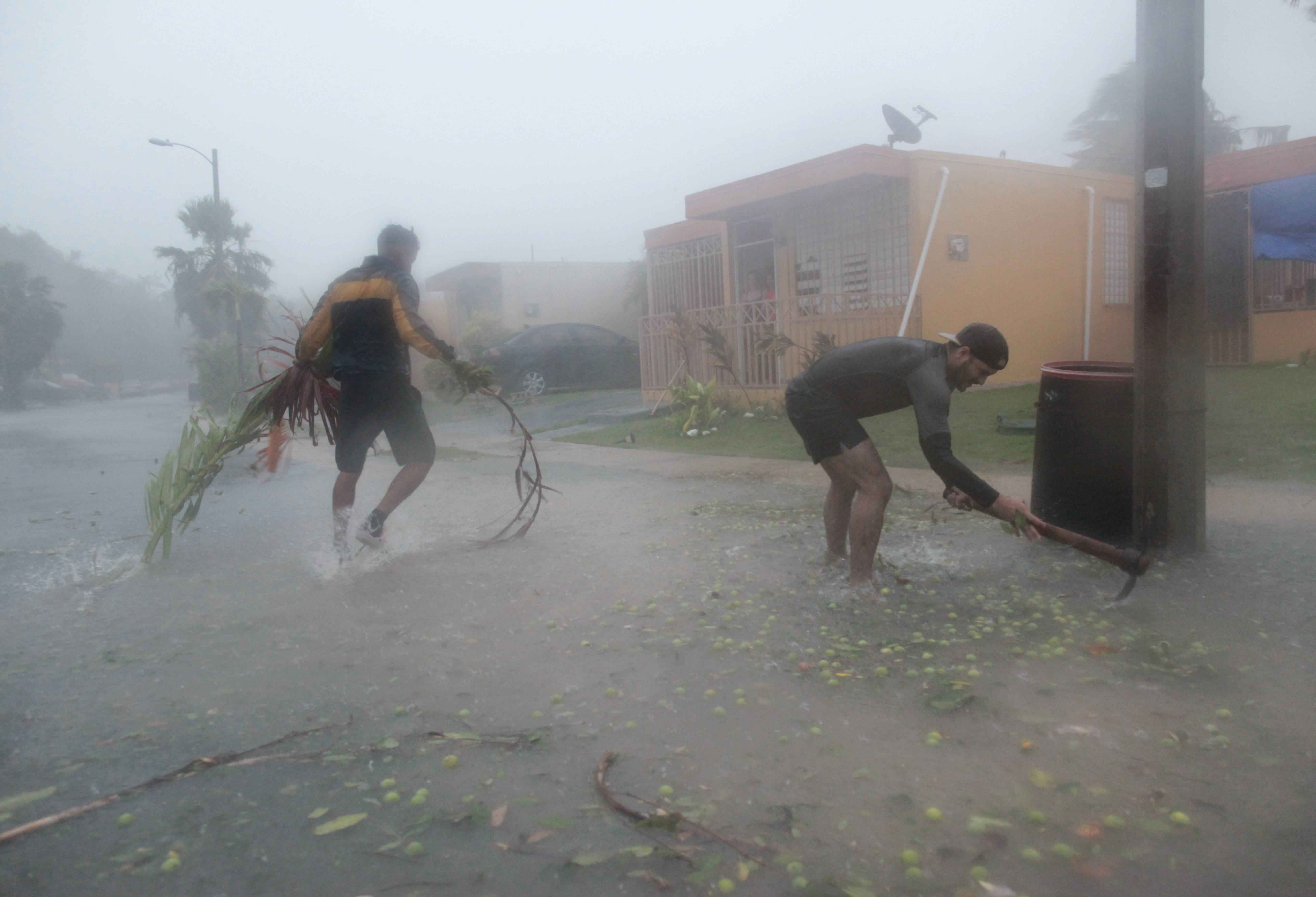 People pick up debris as Hurricane Irma howled past Puerto Rico after thrashing several smaller Caribbean islands, in Fajardo, Puerto Rico on September 6, 2017.