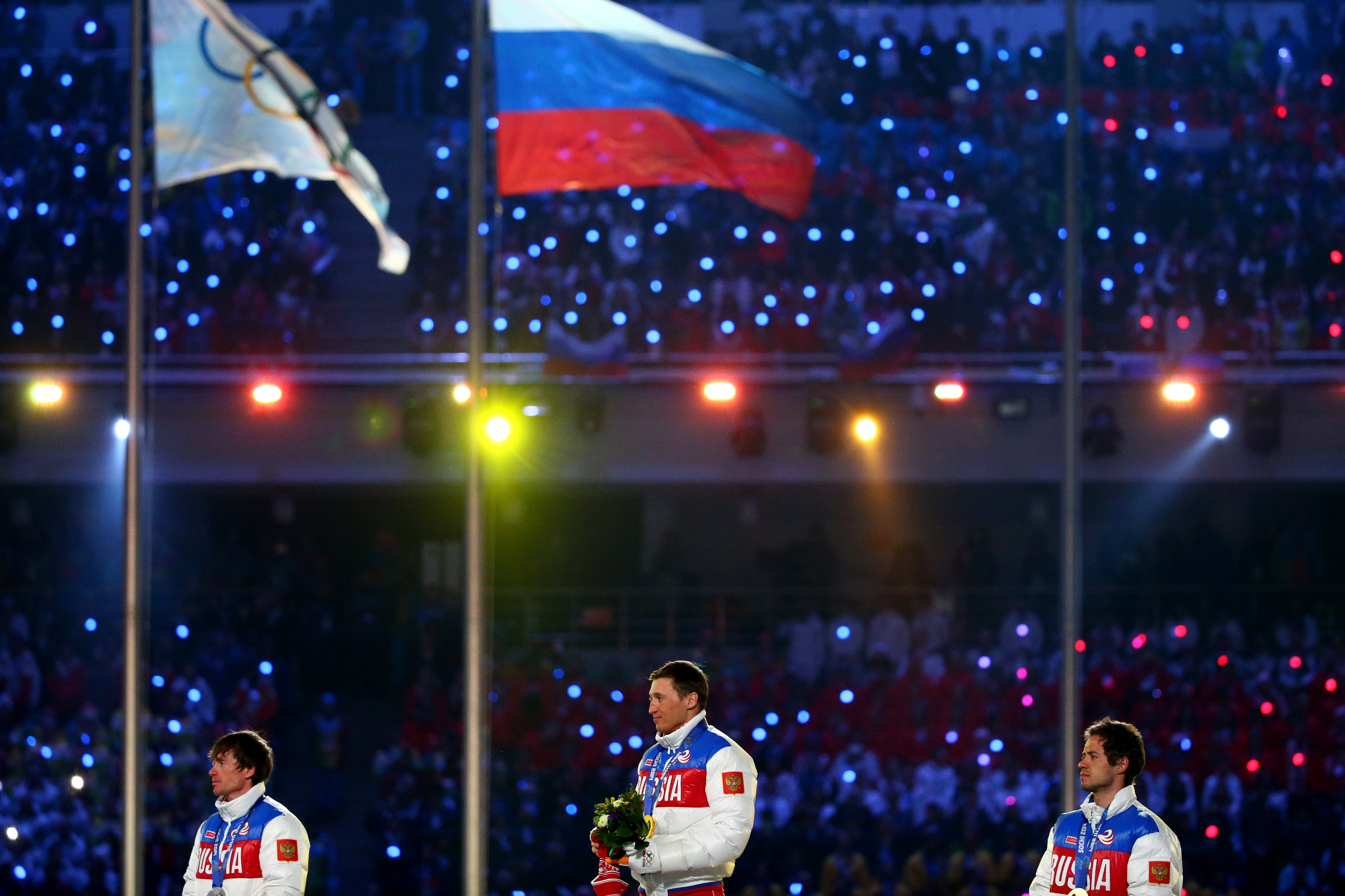 Silver medalist Maxim Vylegzhanin of Russia, gold medalist Alexander Legkov of Russia and bronze medalist Ilia Chernousov of Russia celebrate in the medal ceremony for the Men's 50 km Mass Start Free during the 2014 Sochi Winter Olympics Closing Ceremony at Fisht Olympic Stadium on February 23, 2014 in Sochi, Russia. (Ryan Pierse—Getty Images)