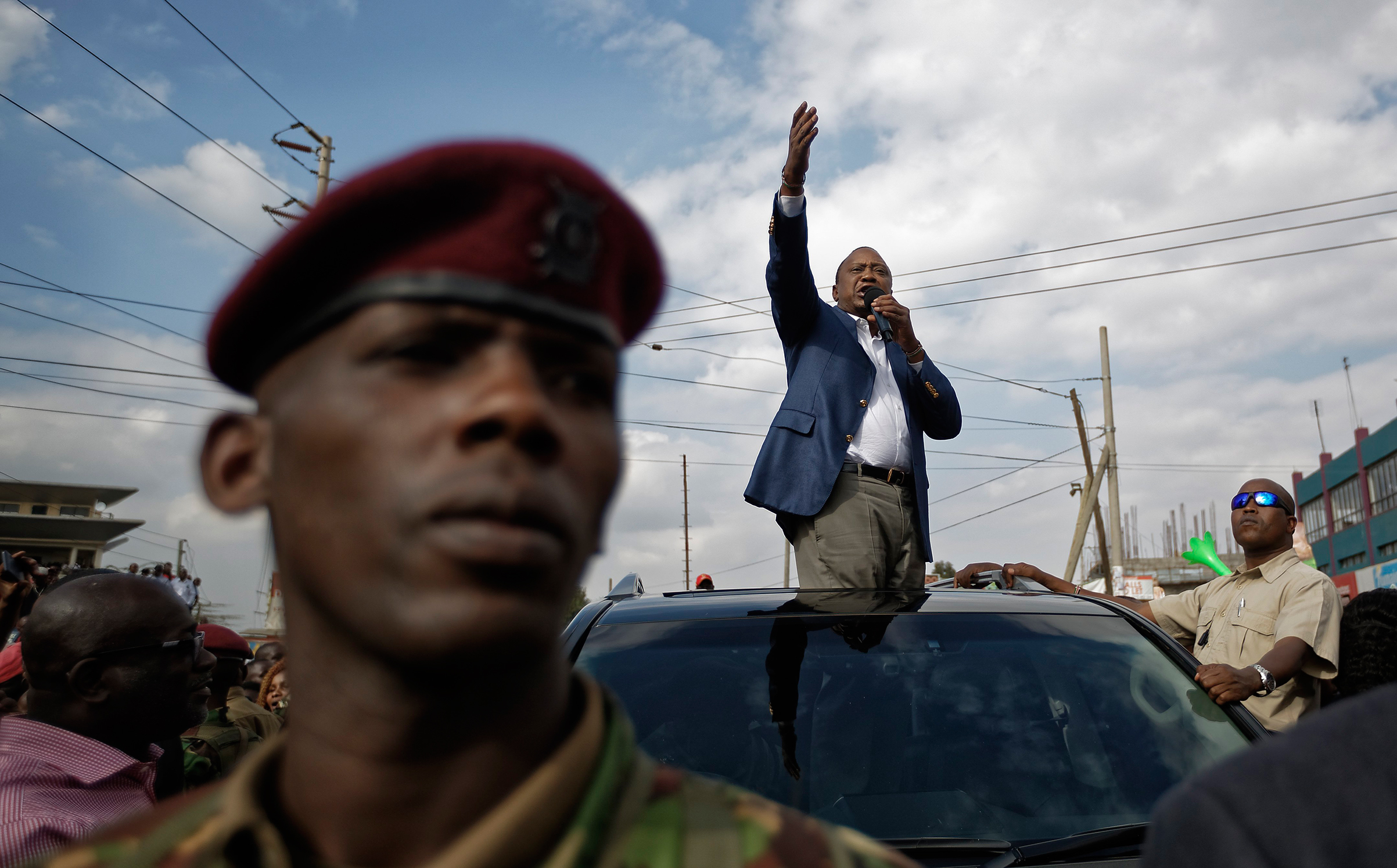 Kenya's President Uhuru Kenyatta, standing through the sunroof of the presidential vehicle, addresses his supporters as a presidential guard provides security, left, on a street in Ongata Rongai, on the outskirts of Nairobi, Kenya, Sept. 5, 2017. Kenya faces an Oct. 17 vote after the Supreme Court nullified Kenyatta's re-election but opposition leader Raila Odinga said Tuesday he does not accept the date, demanding reforms to the electoral commission and other  legal and constitutional guarantees.