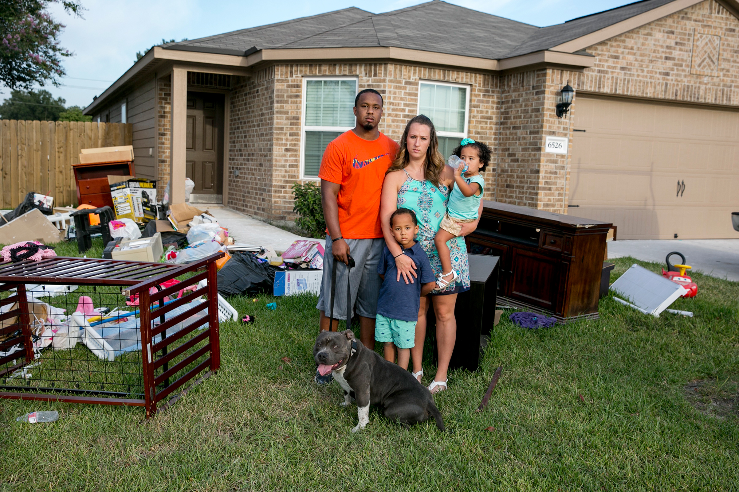 Isiah Courtney stands in the front yard of his Houston home with his wife, Danielle, son Bryson, daughter Aubree and dog Bruce