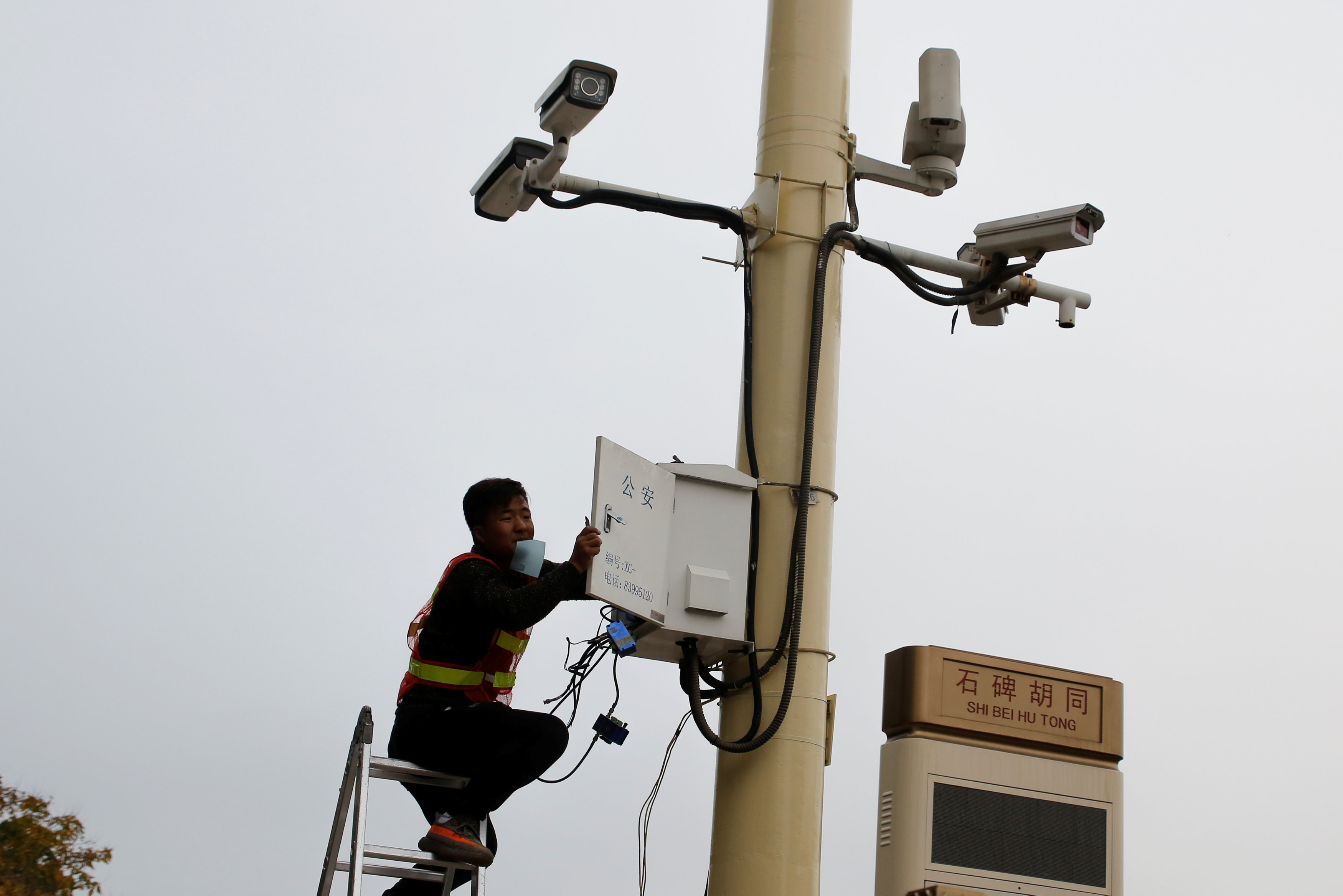 A man works on electrical wires in a box underneath surveillance cameras at Tiananmen Square in Beijing, China, October 12, 2017.