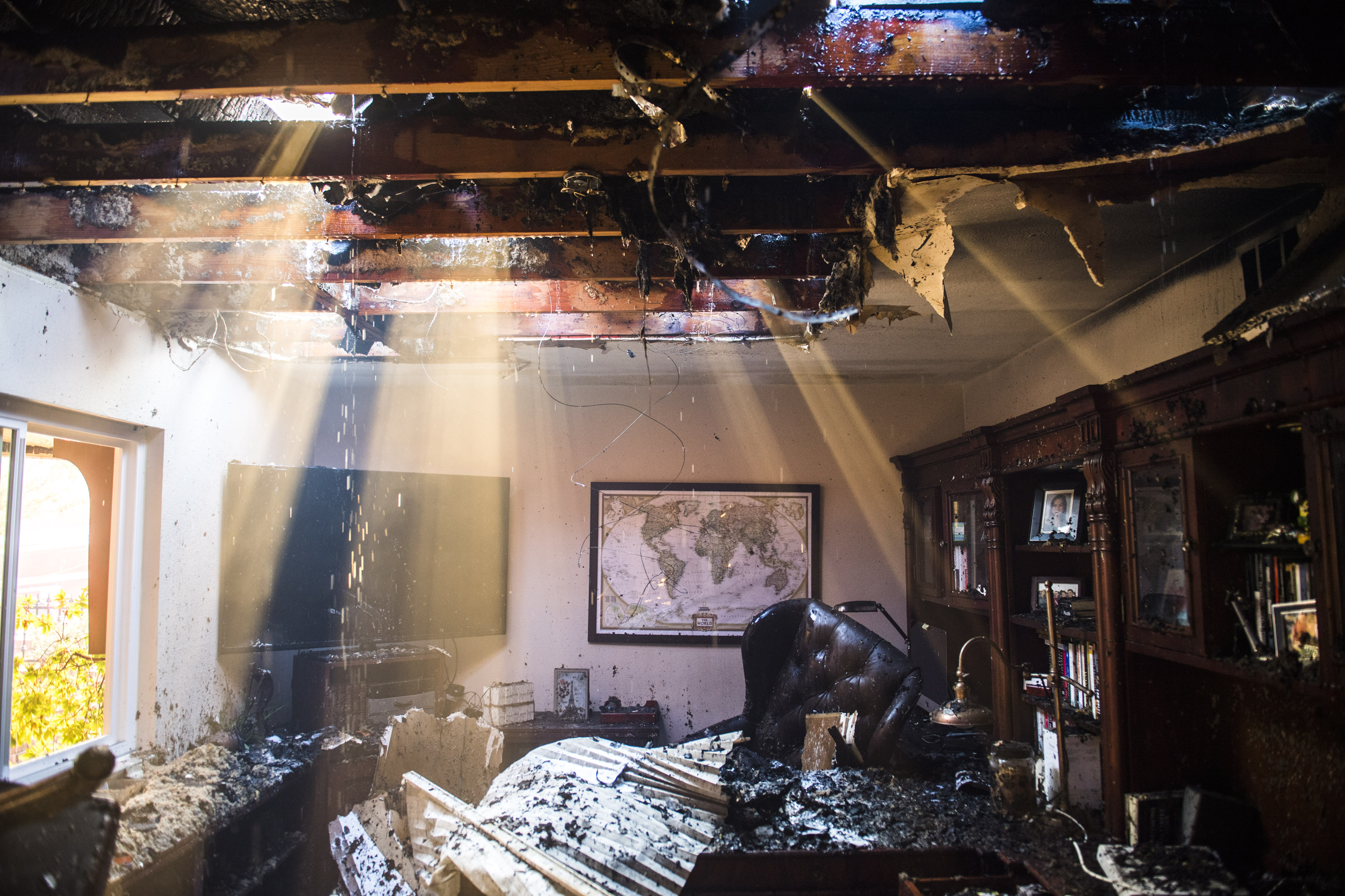 Smoke and water stream through the roof of a damaged home in Anaheim Hills on Oct. 9