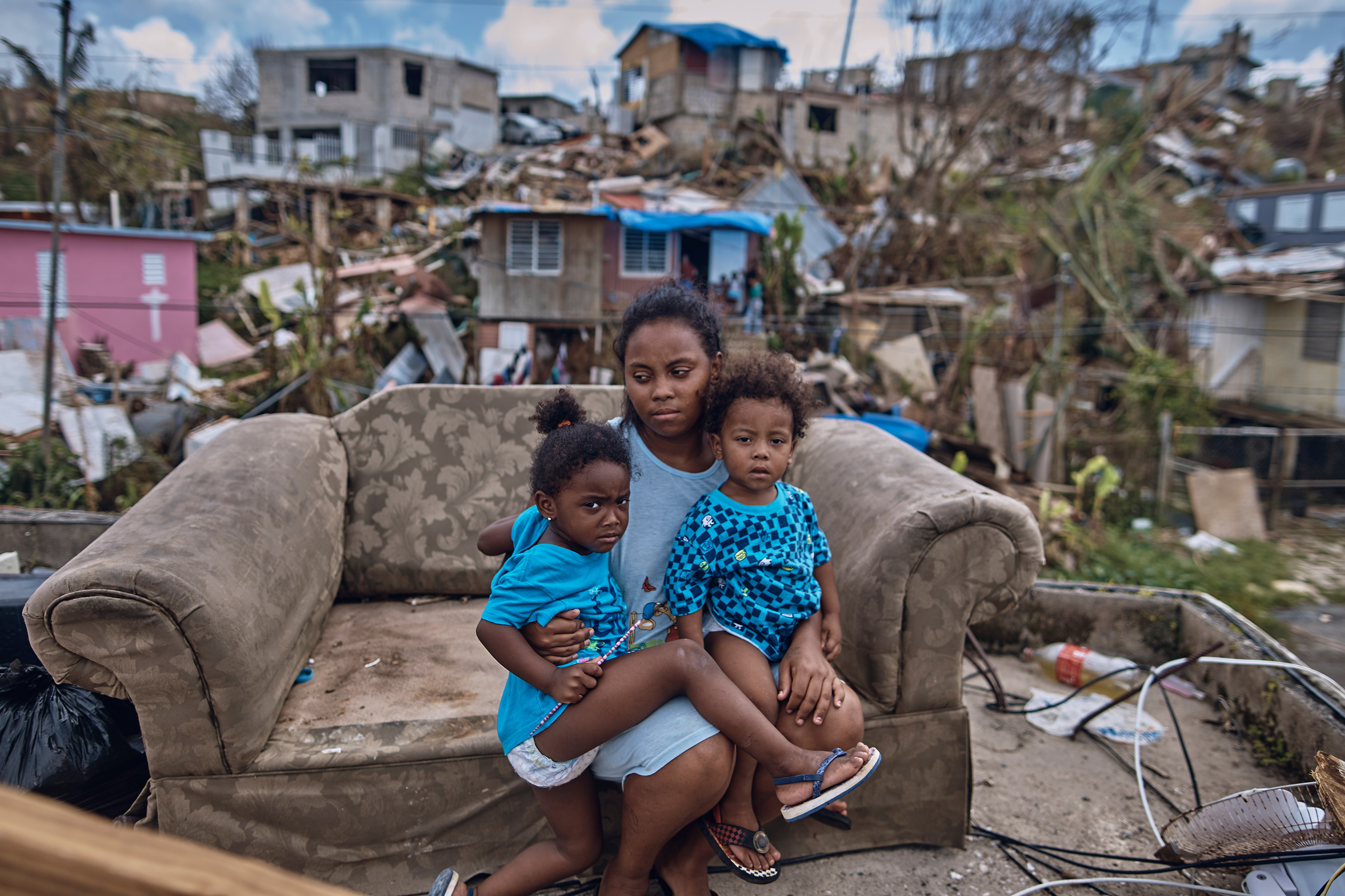 Darieliz Michelle Lopez, her 20-month-old son and three-year-old daughter sit for a portrait on the sofa where her apartment no longer stands in San Isidro, Puerto Rico, on Sept. 28, 2017.