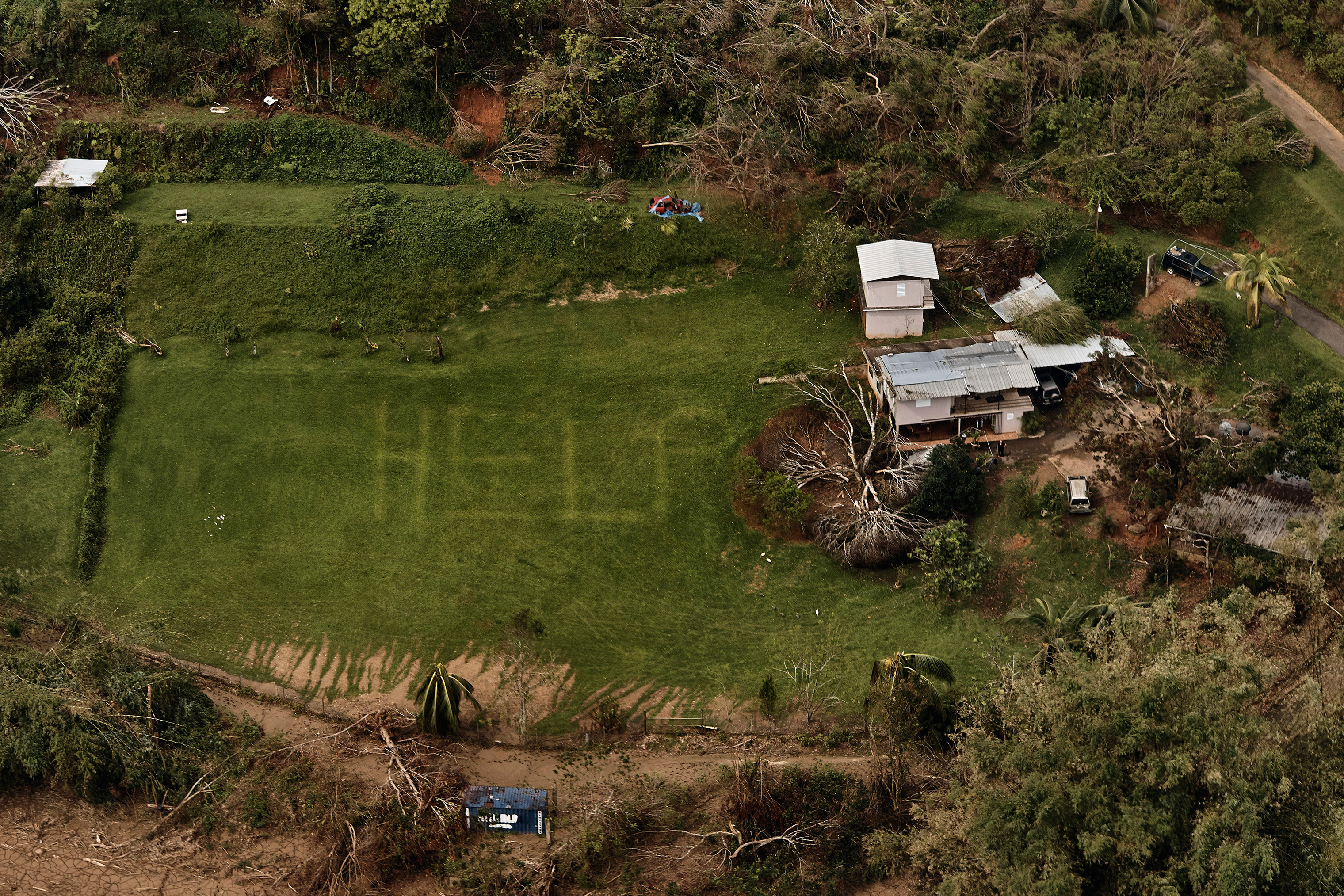 """The desperate message """"HELP"""" is seen on the lawn of a home near Utuado, Puerto Rico, in early October."""