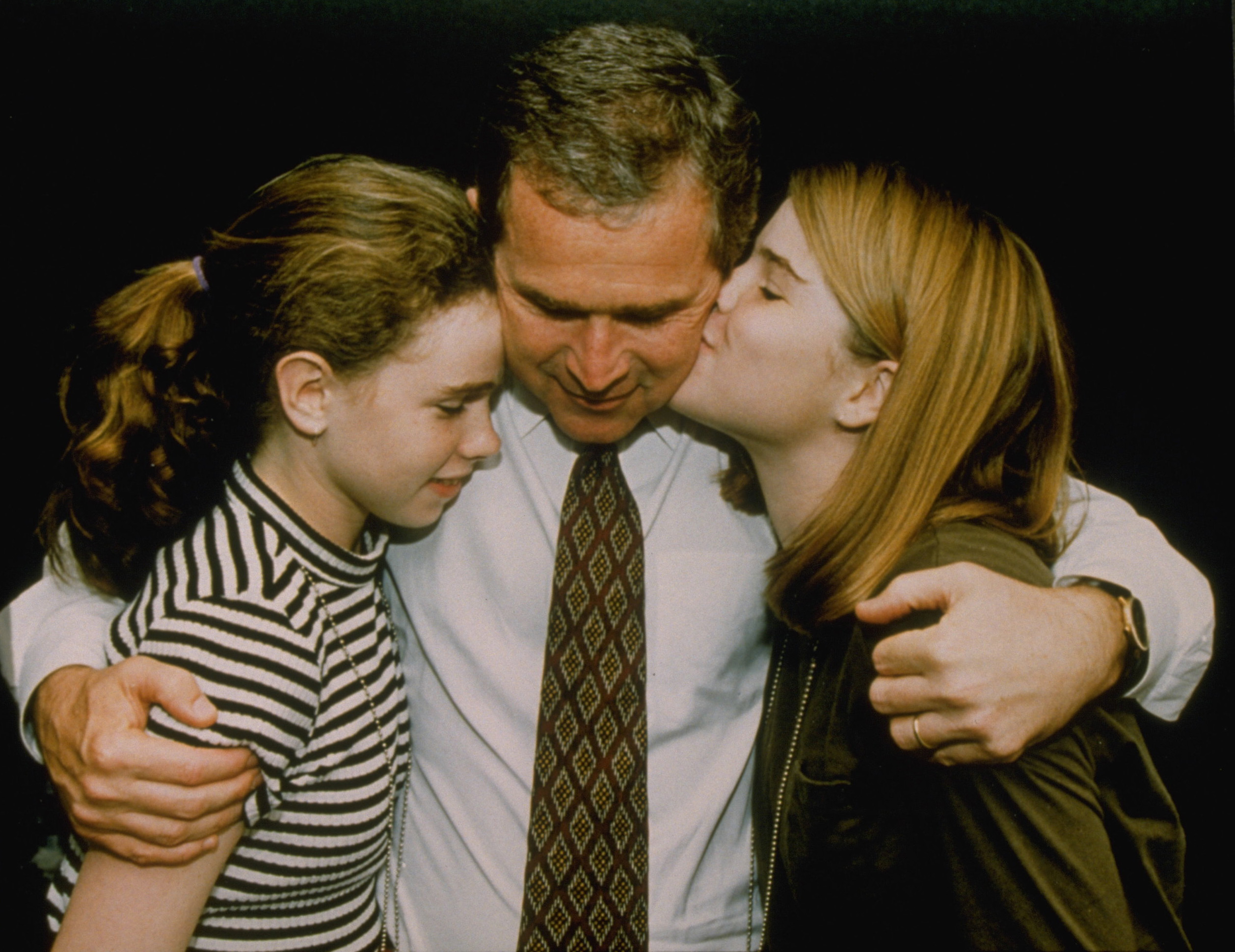 George W. Bush hugging his daughters Barbara and Jenna.