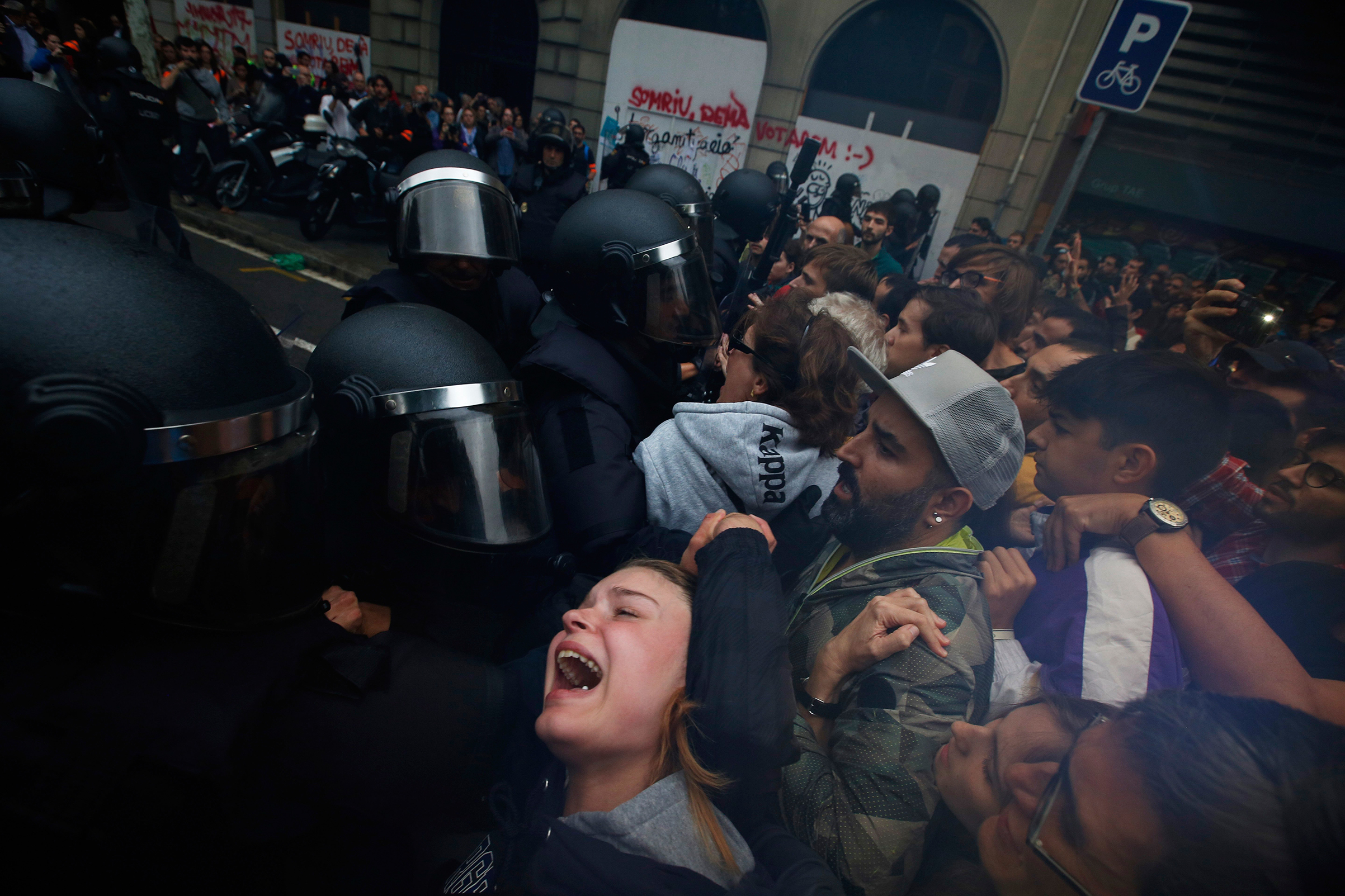 A girl reacts as Spanish National Police push away pro-referendum supporters outside the Ramon Llull school, assigned to be a polling station by the Catalan government, in Barcelona on Oct. 1, 2017.